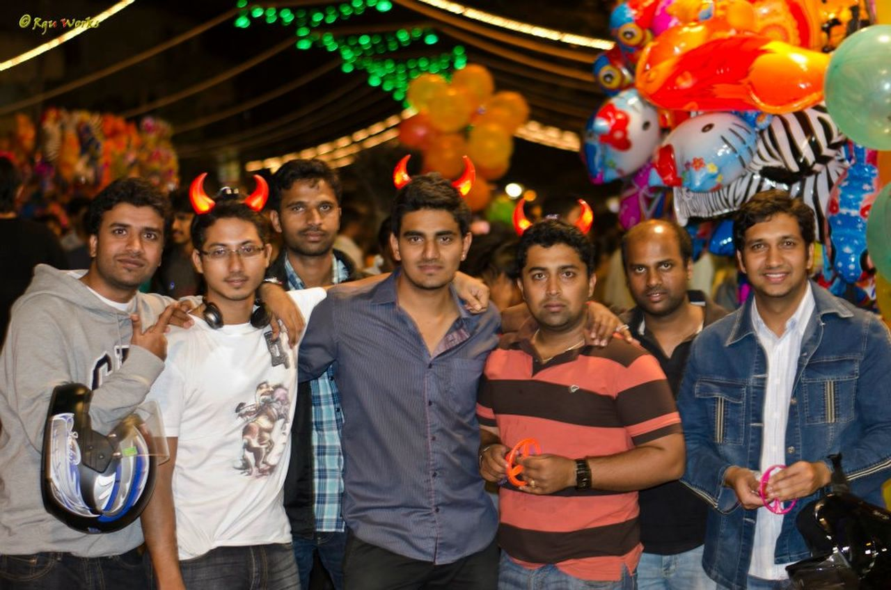 young adult, looking at camera, mid adult, young men, mid adult men, front view, portrait, men, medium group of people, standing, togetherness, young women, smiling, celebration, night, holding, balloon, friendship, outdoors, well-dressed, nightlife, women, adult, people, adults only