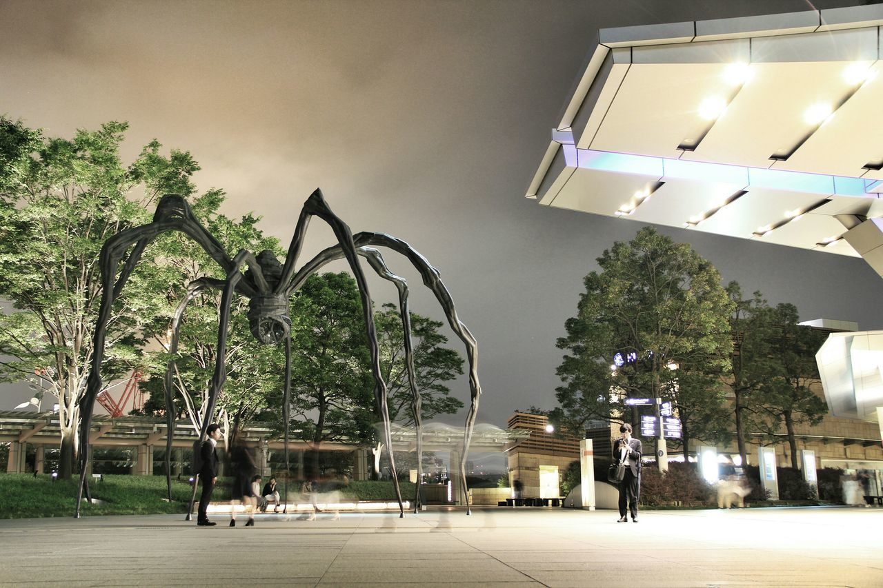 Nightly passersby at the Maman-Spider of Tokyo | Tokyo Japan Roppongi Hills Nightphotography Night Louise Bourgeois Maman Spider ArtWork People Watching Long Exposure Movement Moving Standstill Streetphotography Passersby Travel Feel The Journey City Life Cityscapes