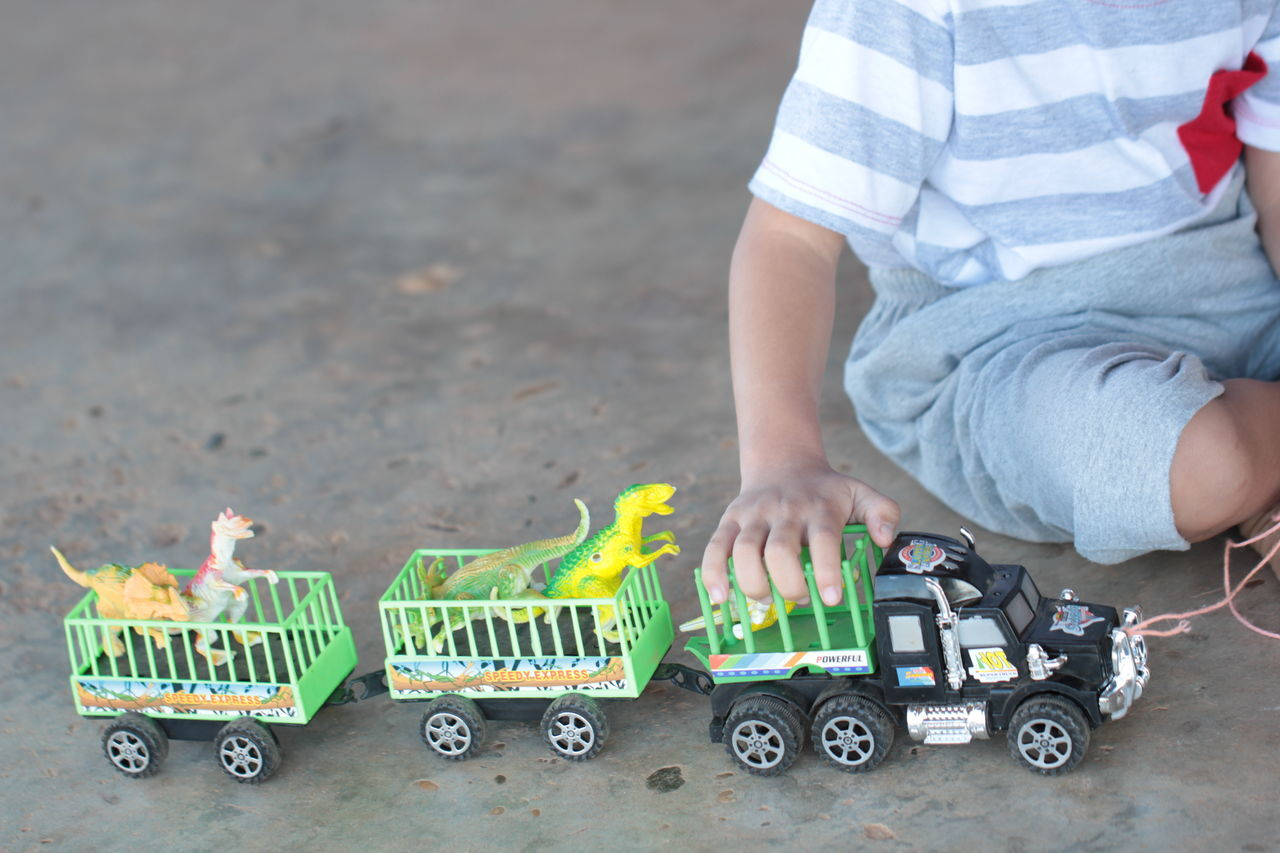 toy, childhood, real people, toy car, one person, day, outdoors, low section, people