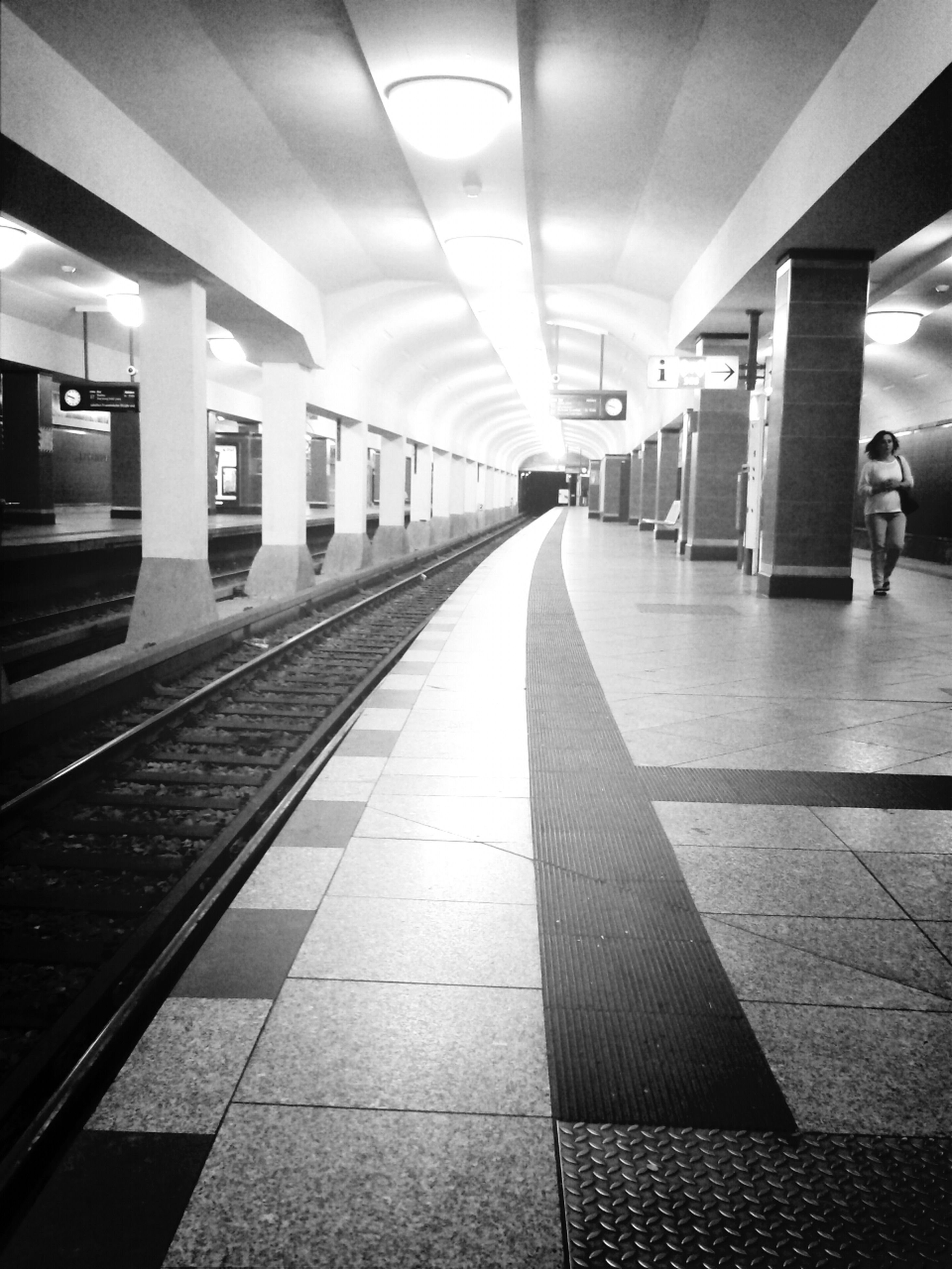 indoors, ceiling, the way forward, transportation, illuminated, railroad station platform, architecture, built structure, tiled floor, diminishing perspective, subway station, incidental people, railroad station, flooring, public transportation, subway, empty, rail transportation, vanishing point, architectural column