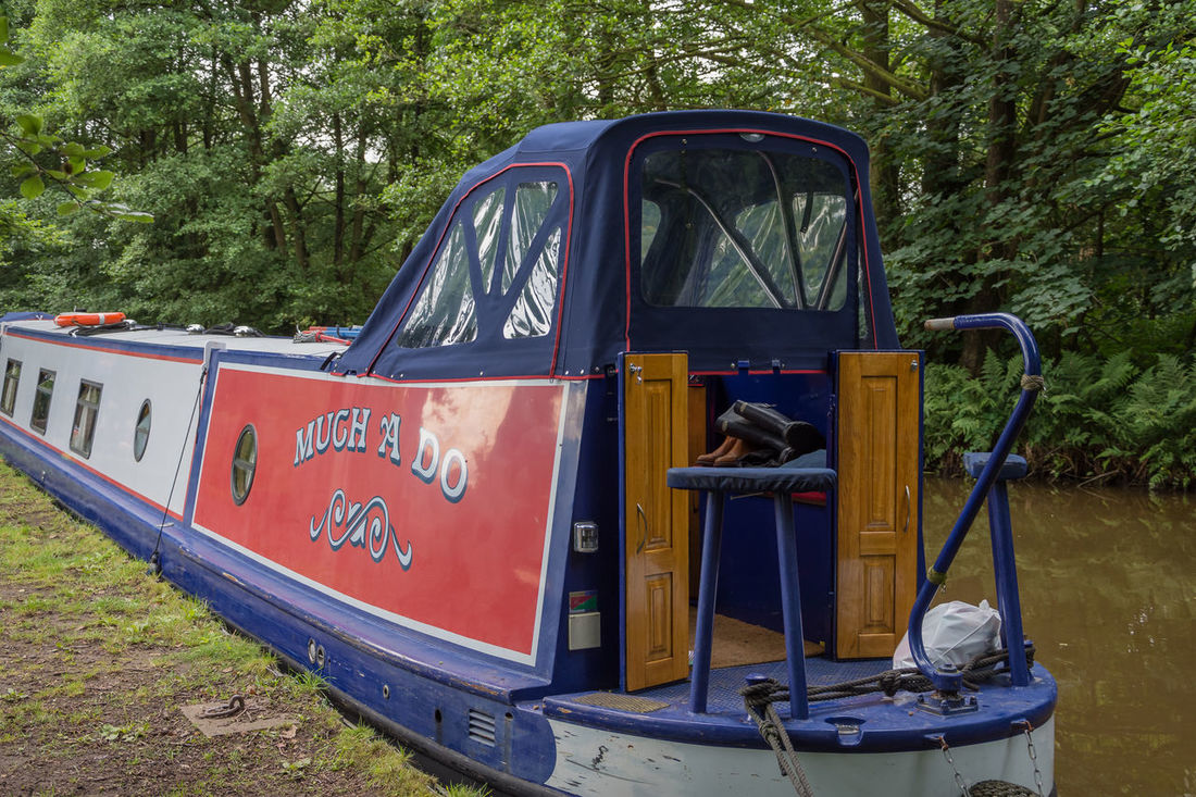 close up of barge boat on the canal Barge BargeOnTheRiver Boots Green Hiking Nature Red Tree Barge Boat House Barge Canal Barge Tied Up Blue Bushes Day Door Ellesmere Lake Lake Nature No People Outdoor Photography Outdoors Outdoors Photograpghy  Tree Water Waterfront