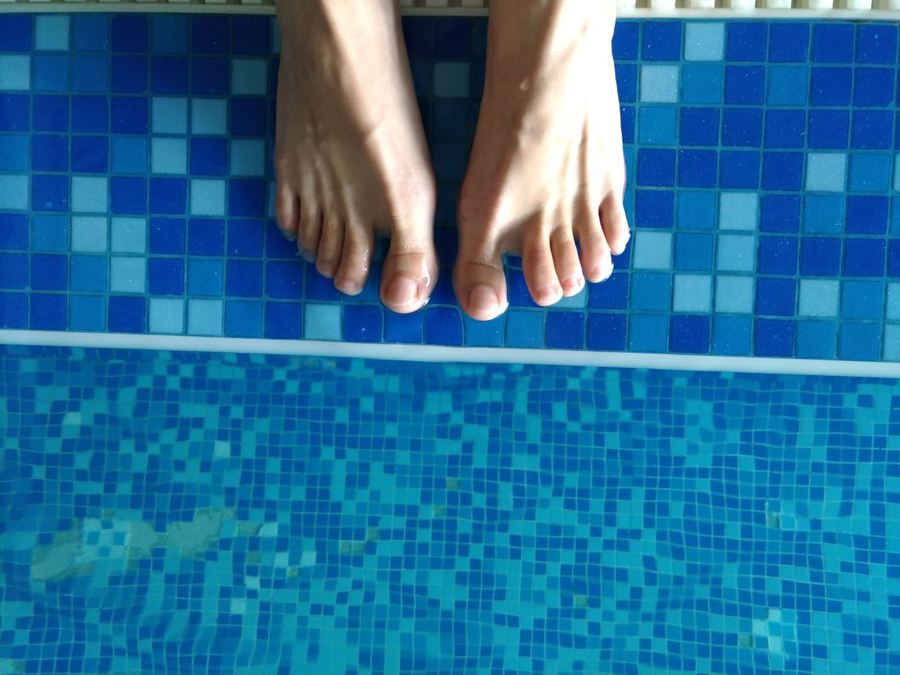 swimming pool, human body part, tile, human foot, low section, barefoot, domestic bathroom, one person, human leg, water, bathroom, indoors, blue, women, close-up, domestic room, day, one woman only, adult, human hand, people, adults only