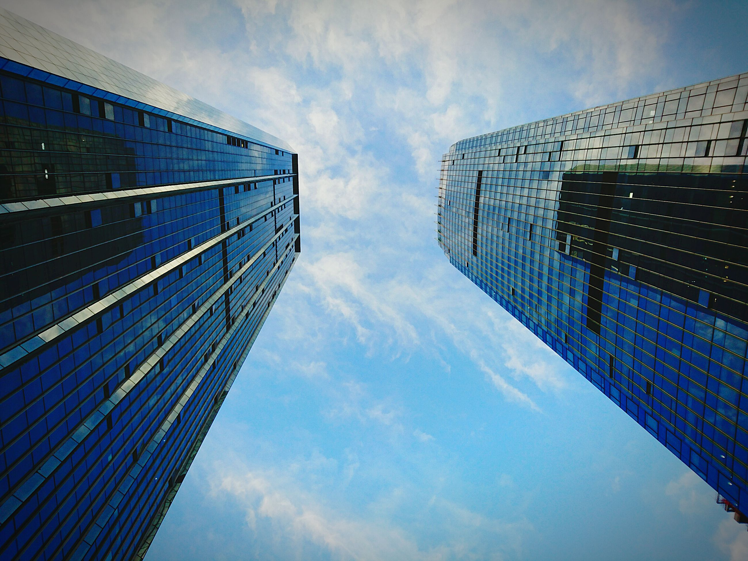 architecture, built structure, sky, building exterior, low angle view, cloud - sky, modern, blue, city, office building, cloudy, cloud, reflection, skyscraper, building, tall - high, day, outdoors, tower, no people