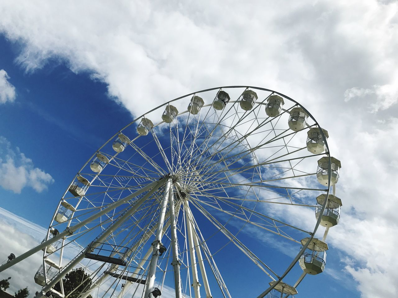 amusement park, arts culture and entertainment, ferris wheel, low angle view, fairground ride, sky, big wheel, amusement park ride, cloud - sky, blue, day, no people, leisure activity, outdoors