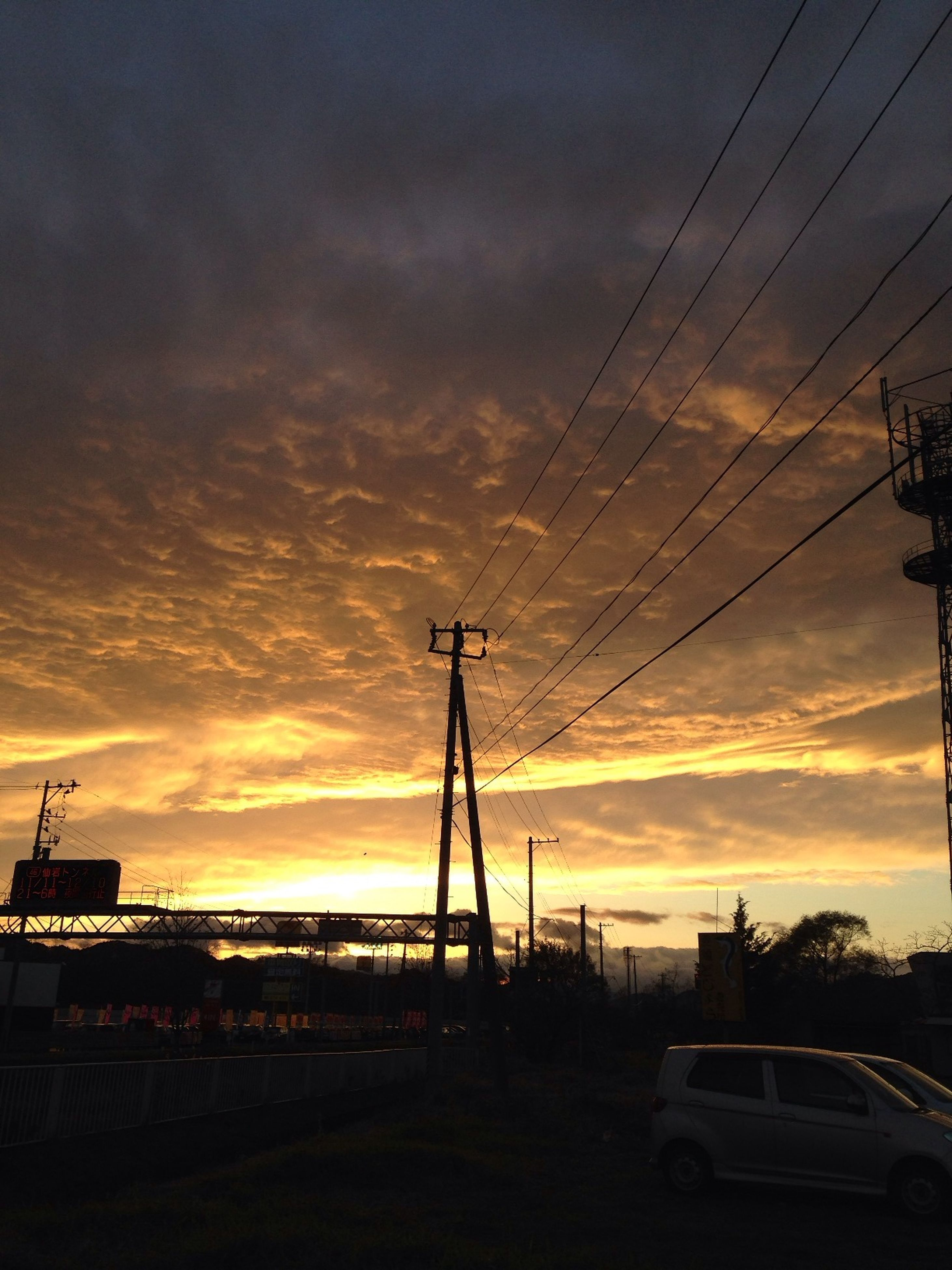 transportation, mode of transport, sky, silhouette, sunset, cloud - sky, power line, electricity pylon, weather, crane - construction machinery, cloudy, dusk, on the move, built structure, travel, outdoors, building exterior, public transportation, nautical vessel, nature