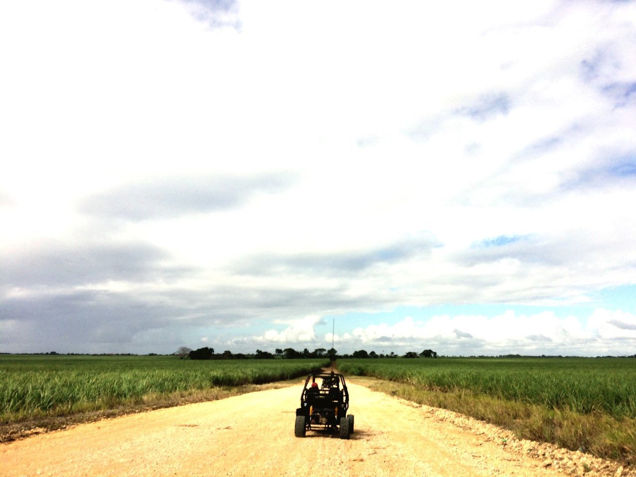 Car On Dirt Road By Agricultural Field Against Sky