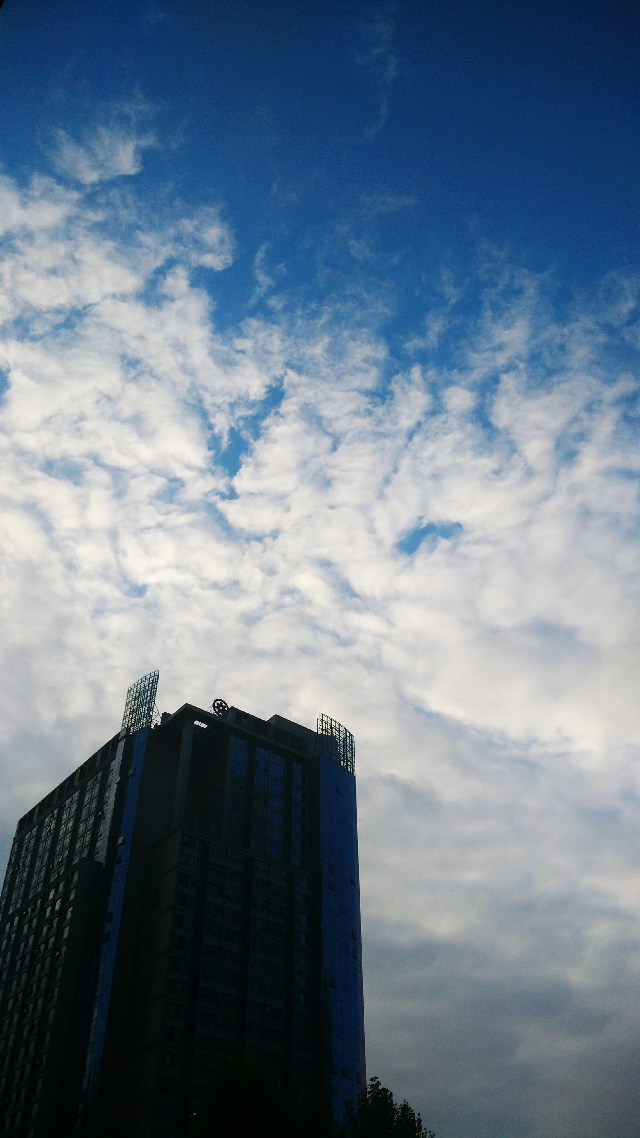 building exterior, architecture, built structure, low angle view, sky, city, skyscraper, office building, modern, tall - high, tower, cloud - sky, building, cloud, blue, cloudy, outdoors, tall, day, no people
