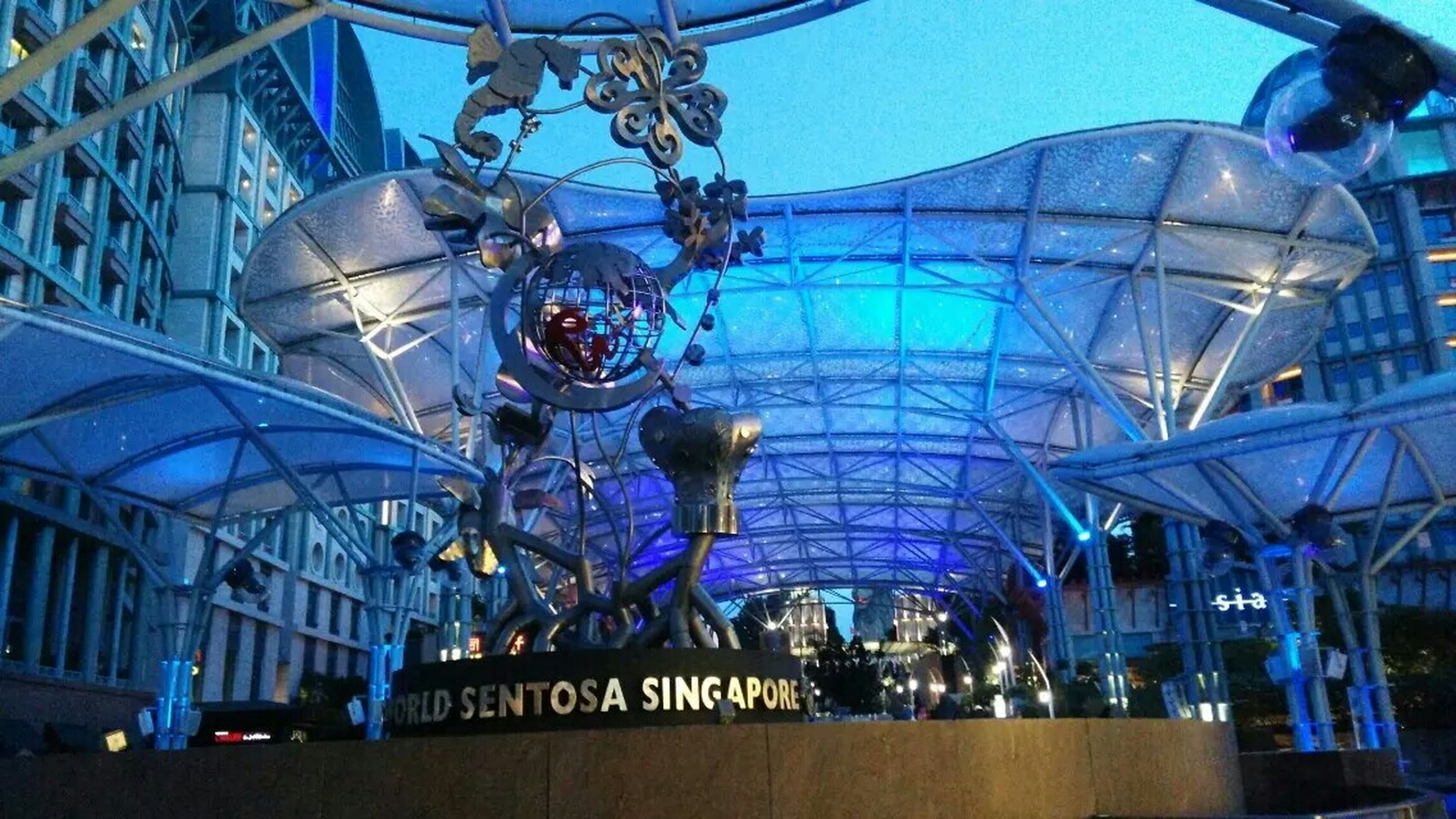 built structure, architecture, low angle view, transportation, lighting equipment, illuminated, building exterior, blue, indoors, amusement park ride, ceiling, amusement park, mode of transport, modern, travel, city, ferris wheel, incidental people, arts culture and entertainment, hanging