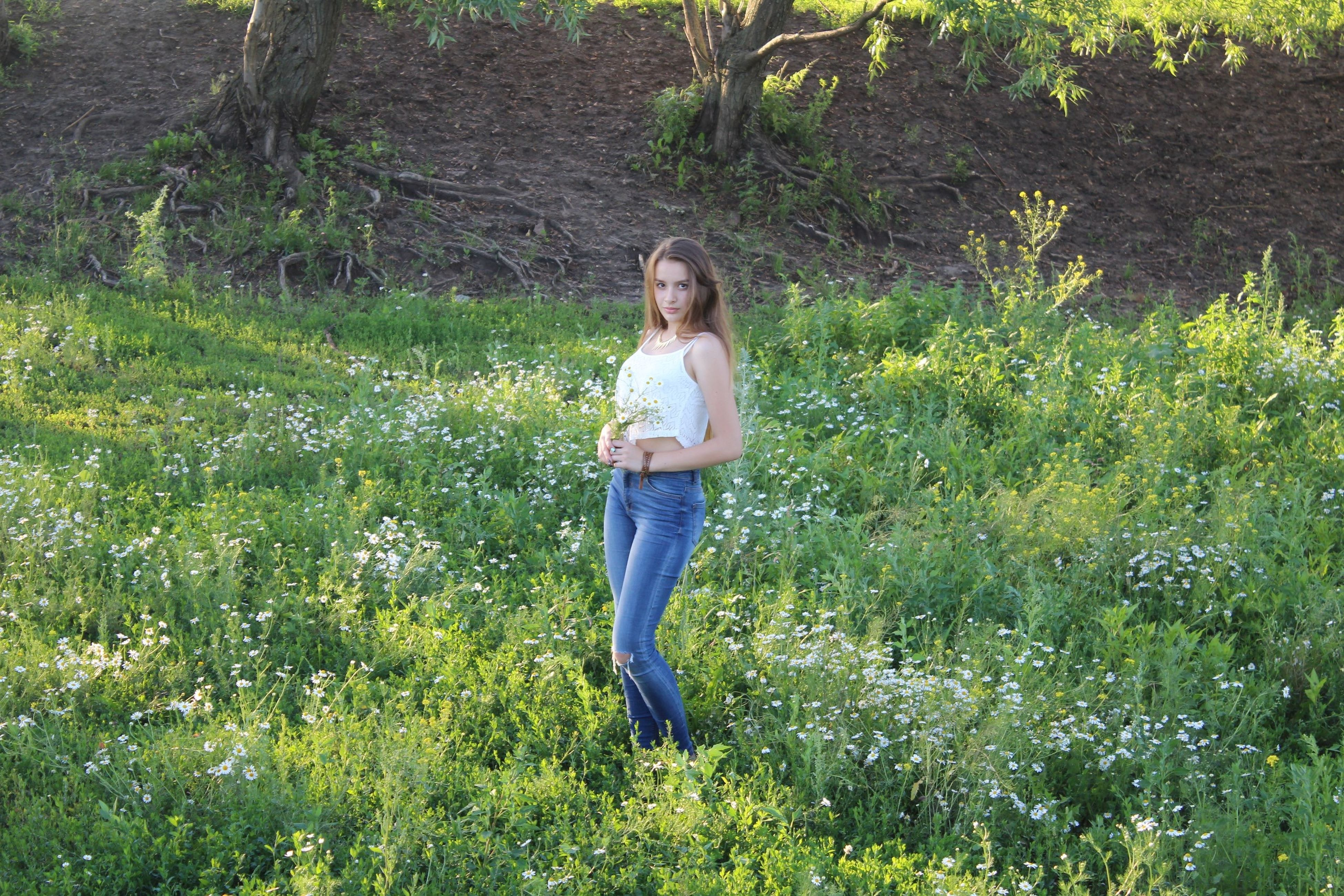 casual clothing, full length, grass, young adult, lifestyles, person, standing, leisure activity, growth, young women, front view, portrait, green color, plant, field, tree, looking at camera, nature