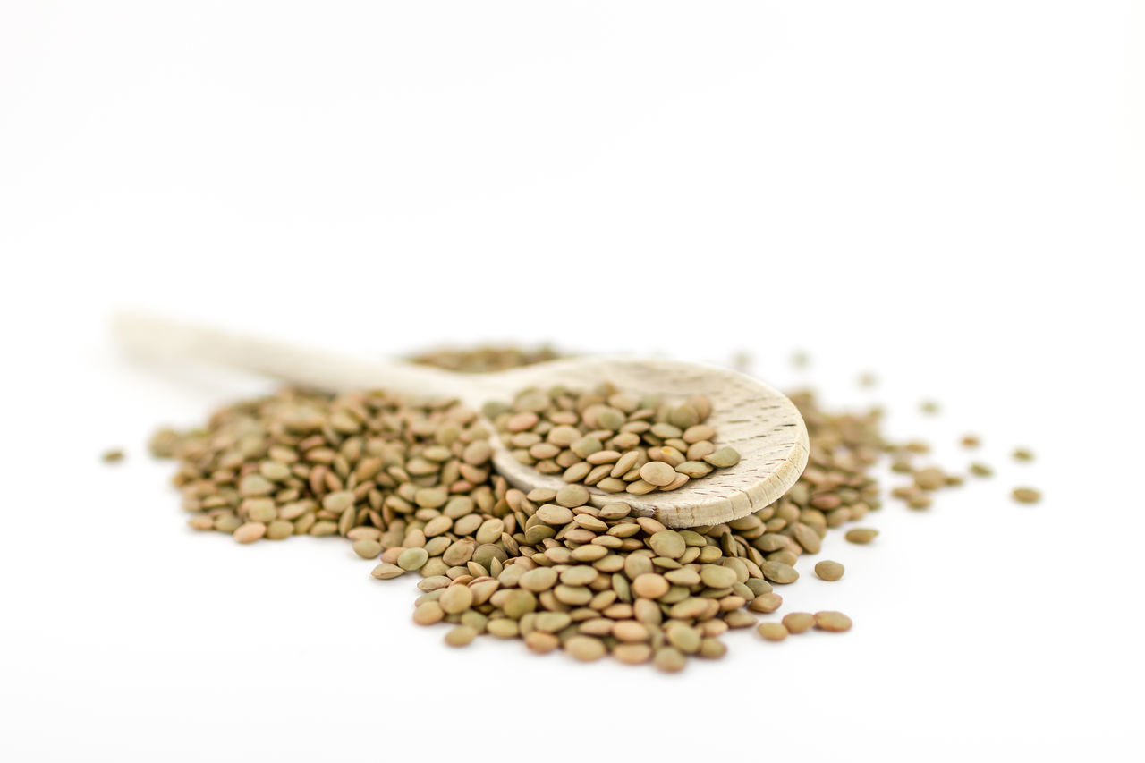 Natural organic dry lentils on white background with wooden spoon. Shallow depth of field. Agricolture Backgrounds Beans Brown Closeup Diet Dietfood Dof Dry Food Grain Healthy Heap Kitchen Legume Lentils Natural Nutrition Organic Protein Raw Seed Spoon Uncooked Vegan