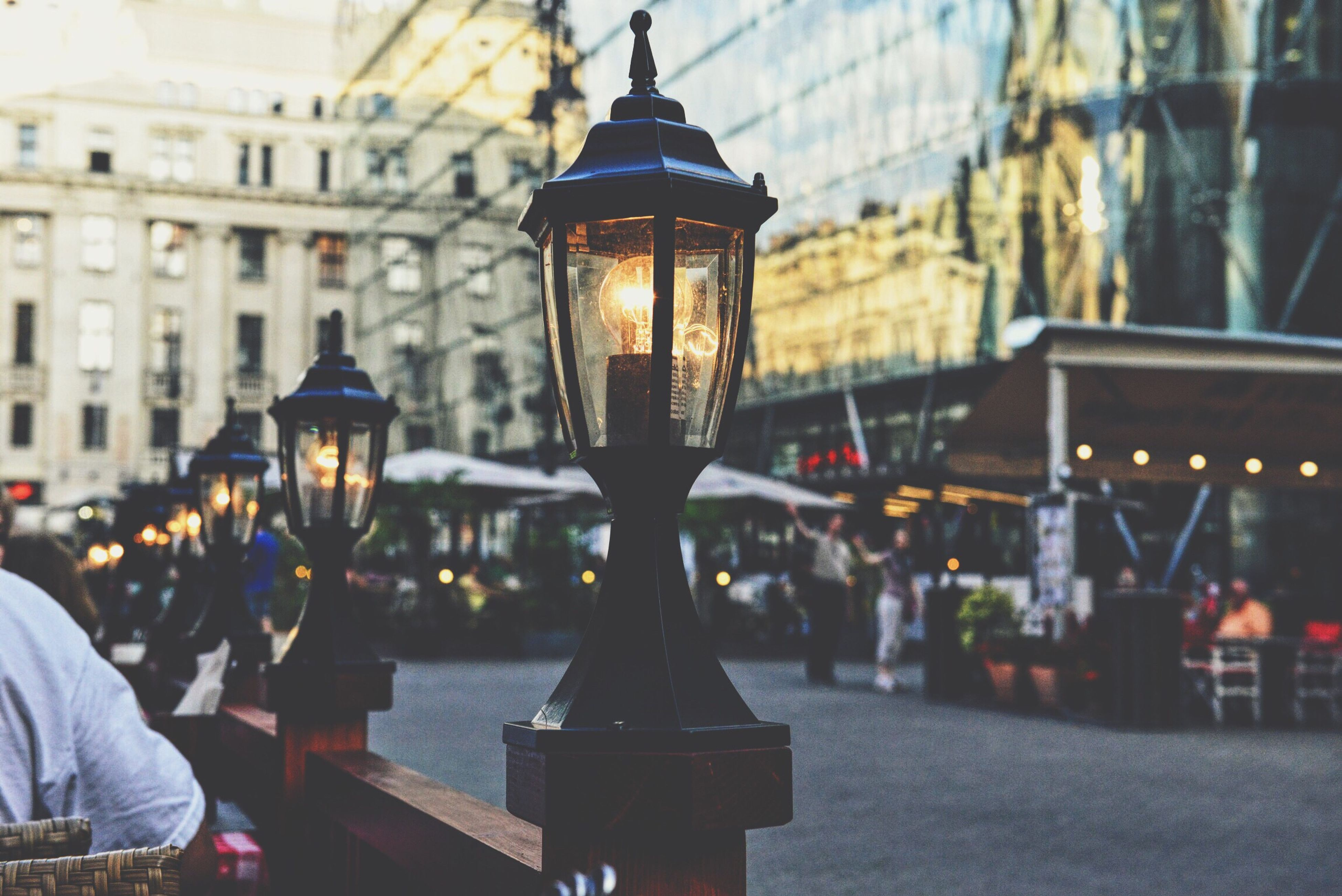 illuminated, focus on foreground, lighting equipment, men, building exterior, architecture, built structure, incidental people, night, selective focus, restaurant, lifestyles, street light, rear view, religion, close-up, dusk, table