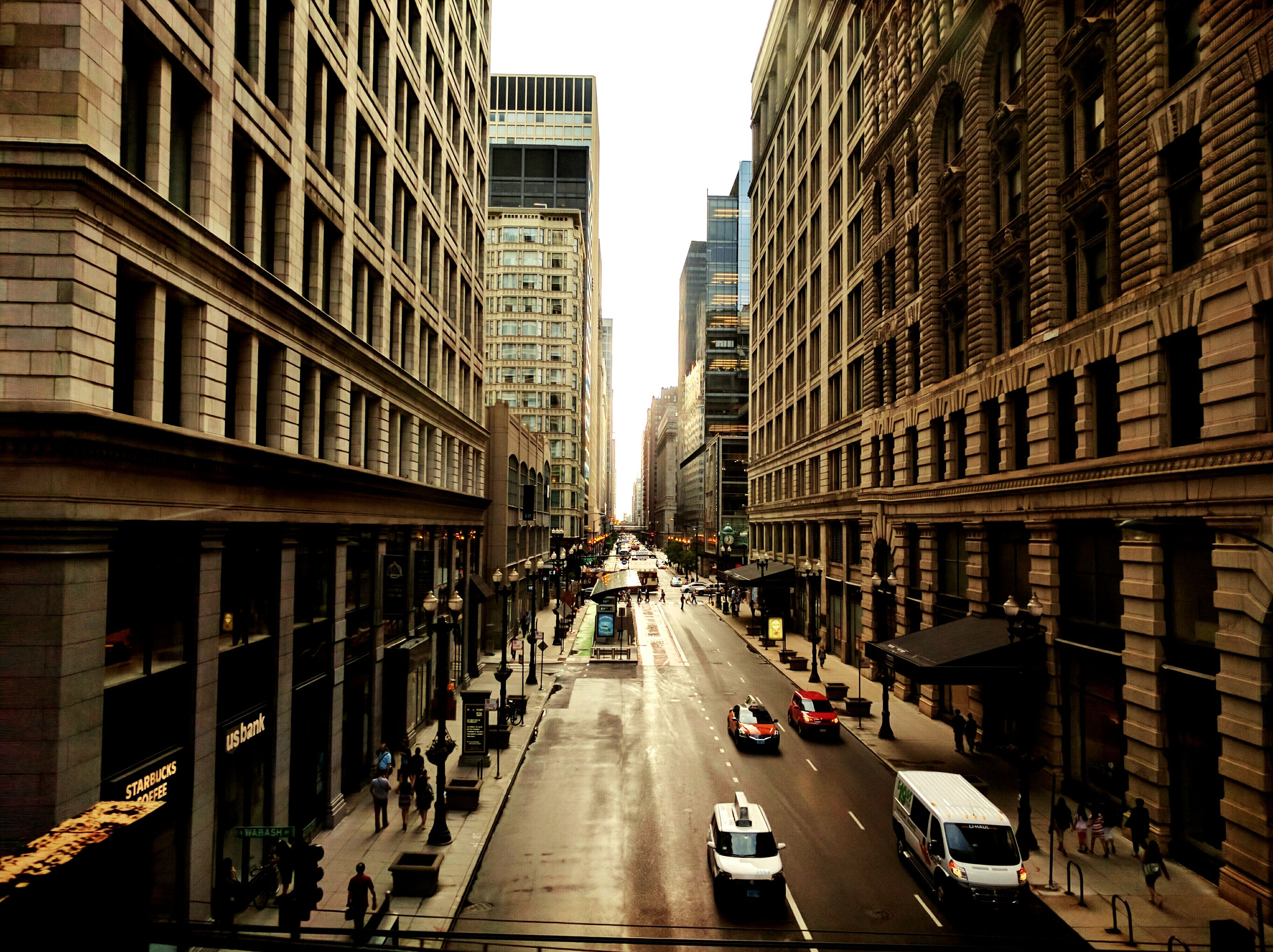 building exterior, architecture, transportation, built structure, car, land vehicle, city, mode of transport, street, the way forward, road, diminishing perspective, city street, city life, incidental people, traffic, building, vanishing point, road marking, vehicle