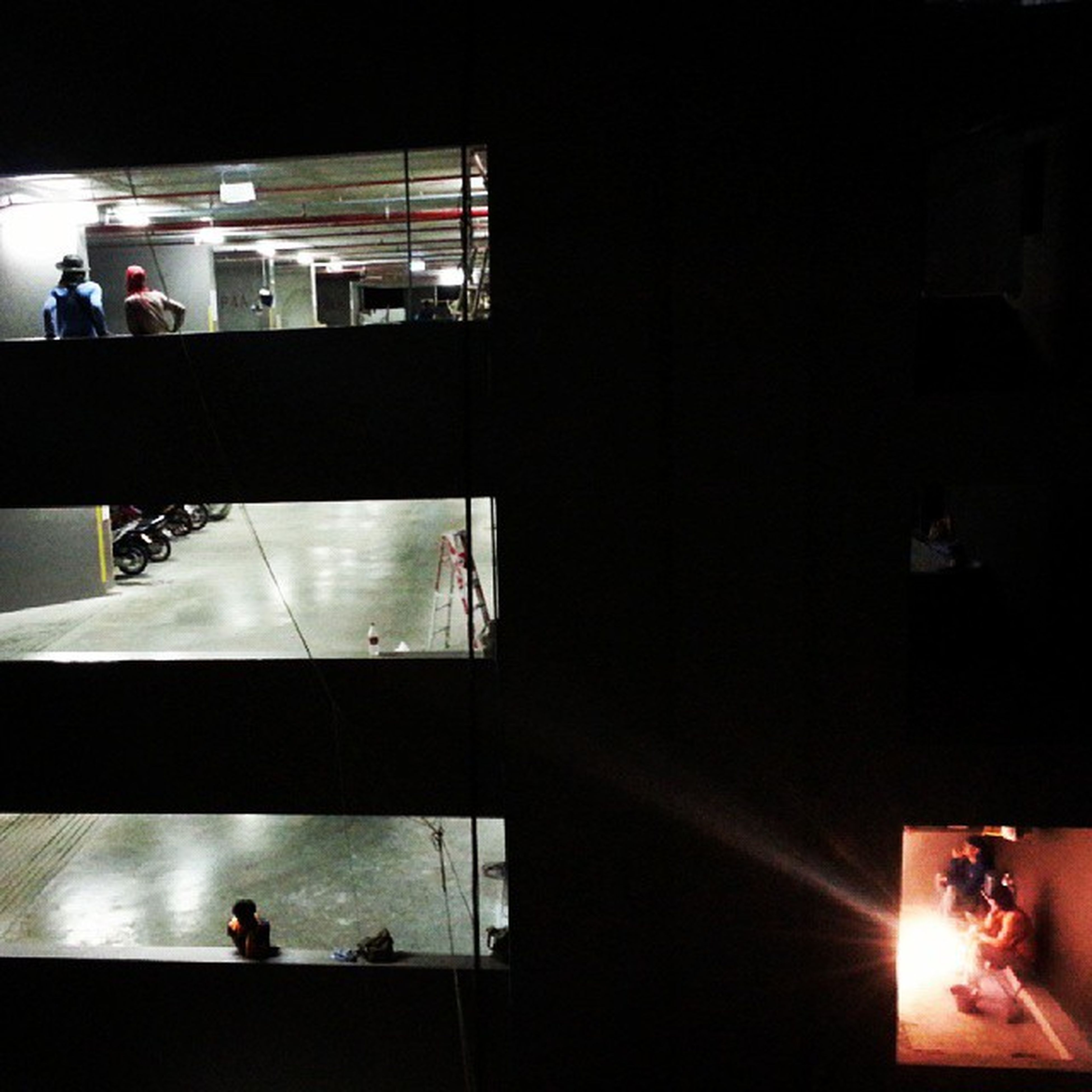 indoors, illuminated, night, built structure, dark, lighting equipment, architecture, window, lifestyles, men, silhouette, leisure activity, glass - material, standing, person, reflection, sitting, incidental people