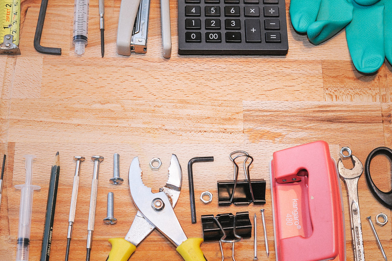 Assorted tools,calculator and stationary on wooden board. Labor Day Spanner Day Directly Above Hand Tool Indoors  Neat No People Occupation Plyers Rubber Gloves Screw Stationary Work Tool Workshop Wrench