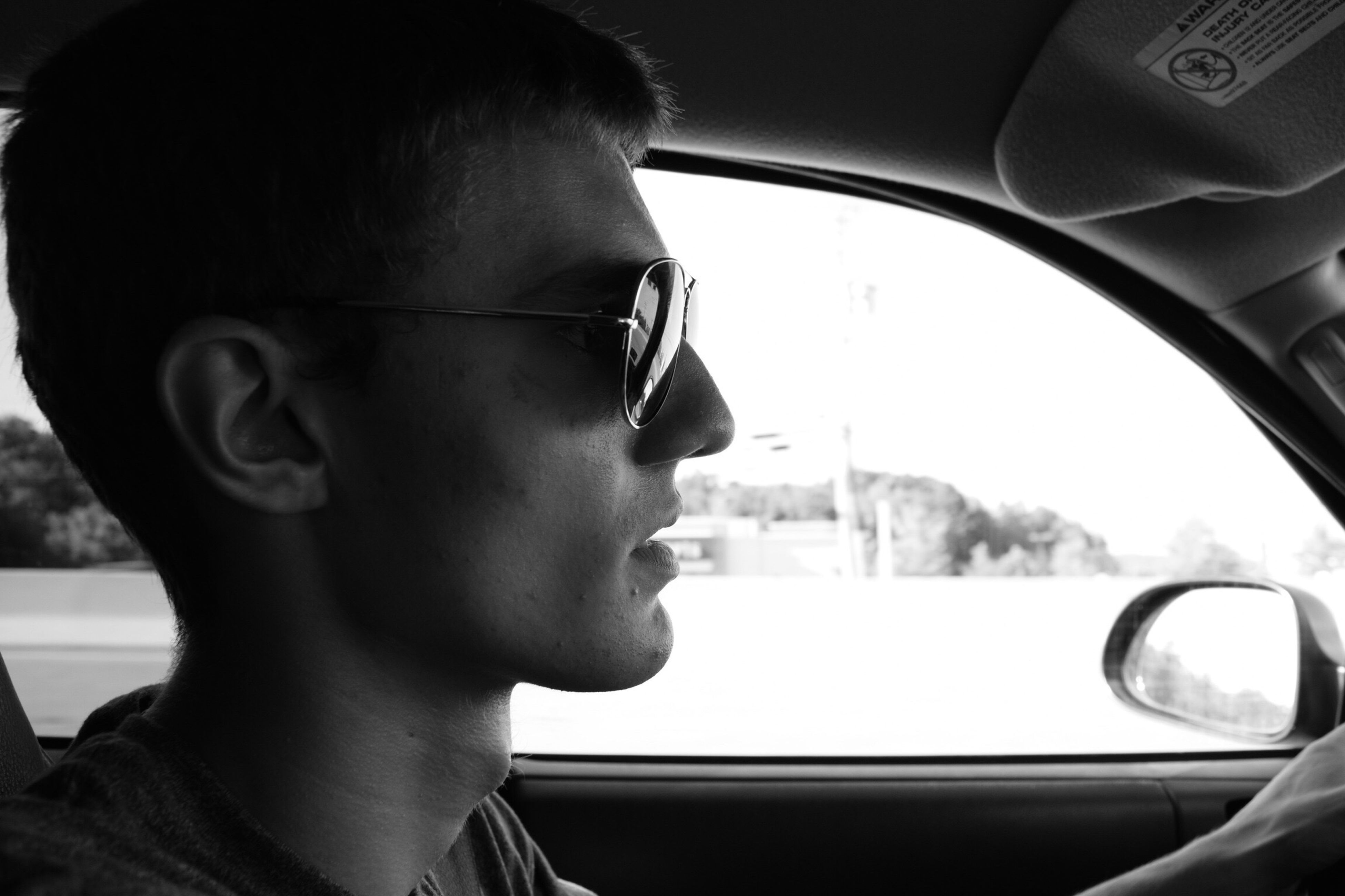 headshot, transportation, car, lifestyles, mode of transport, car interior, close-up, leisure activity, side view, window, vehicle interior, land vehicle, person, looking down, young men, glass - material, young adult, transparent, looking away, day, focus on foreground, serious, profile