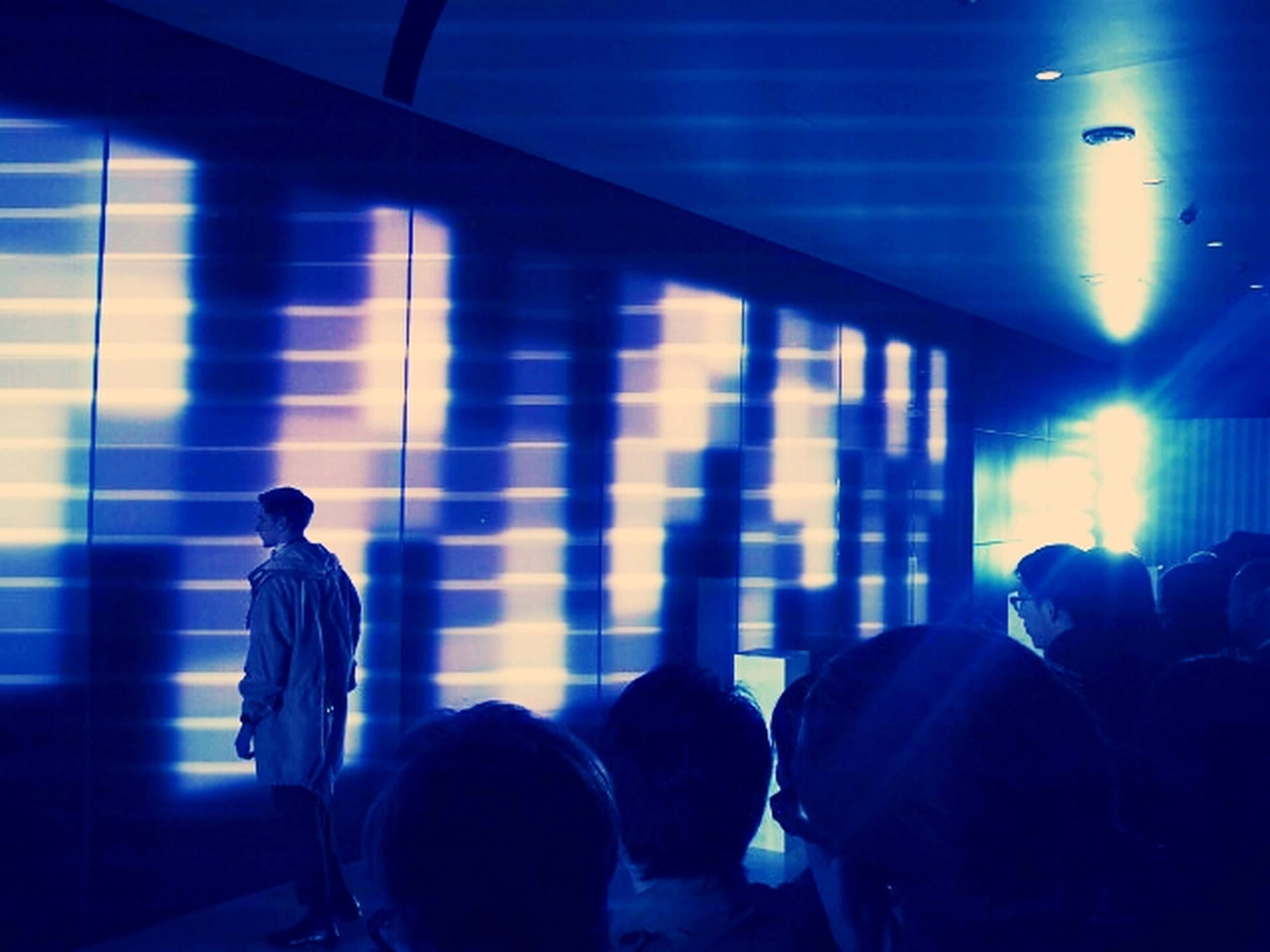 indoors, men, illuminated, lifestyles, silhouette, rear view, person, leisure activity, ceiling, standing, lighting equipment, blue, light - natural phenomenon, dark, togetherness, flooring, arts culture and entertainment, light