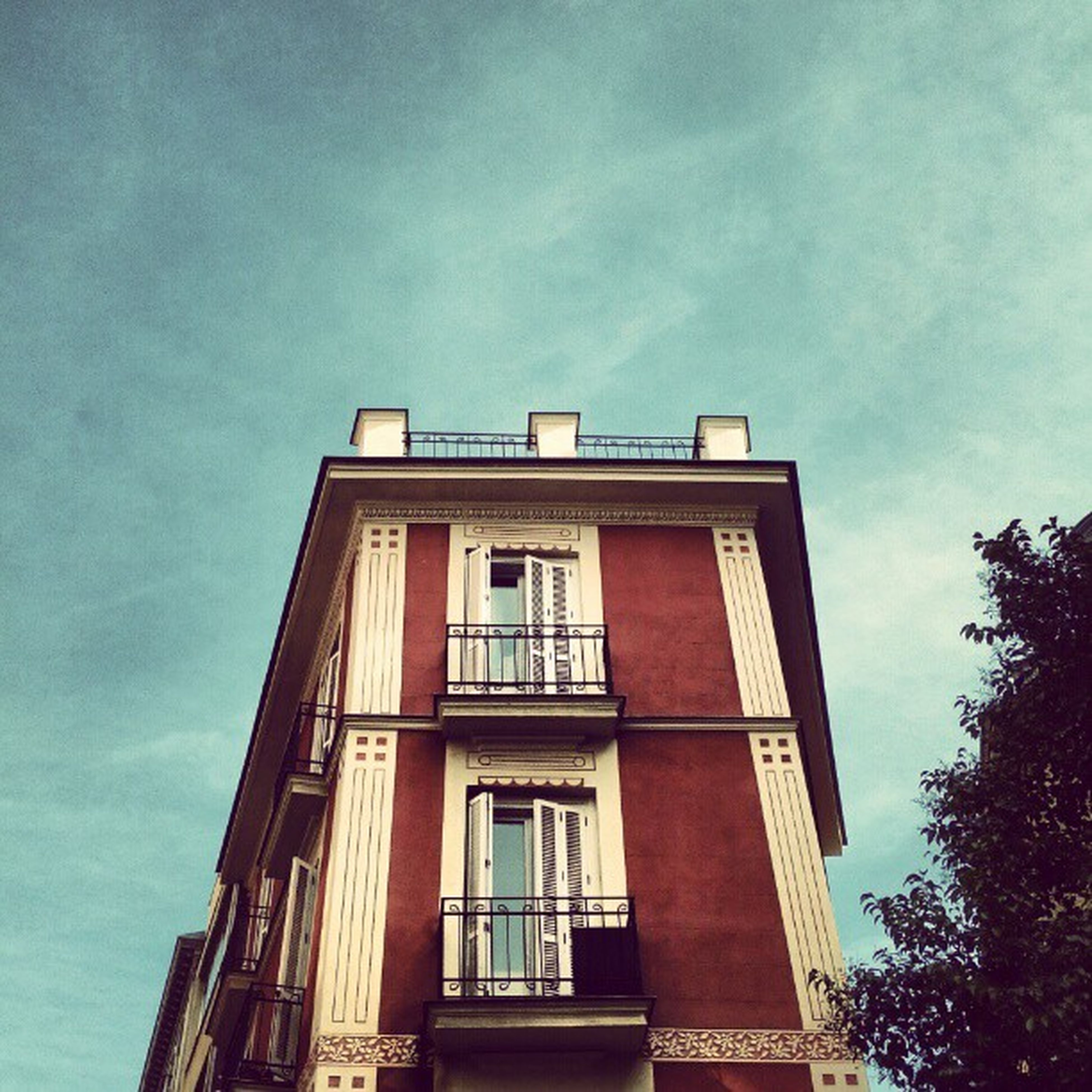 architecture, built structure, building exterior, low angle view, window, sky, building, residential building, residential structure, day, outdoors, cloud - sky, house, no people, city, cloud, balcony, tree, apartment, high section