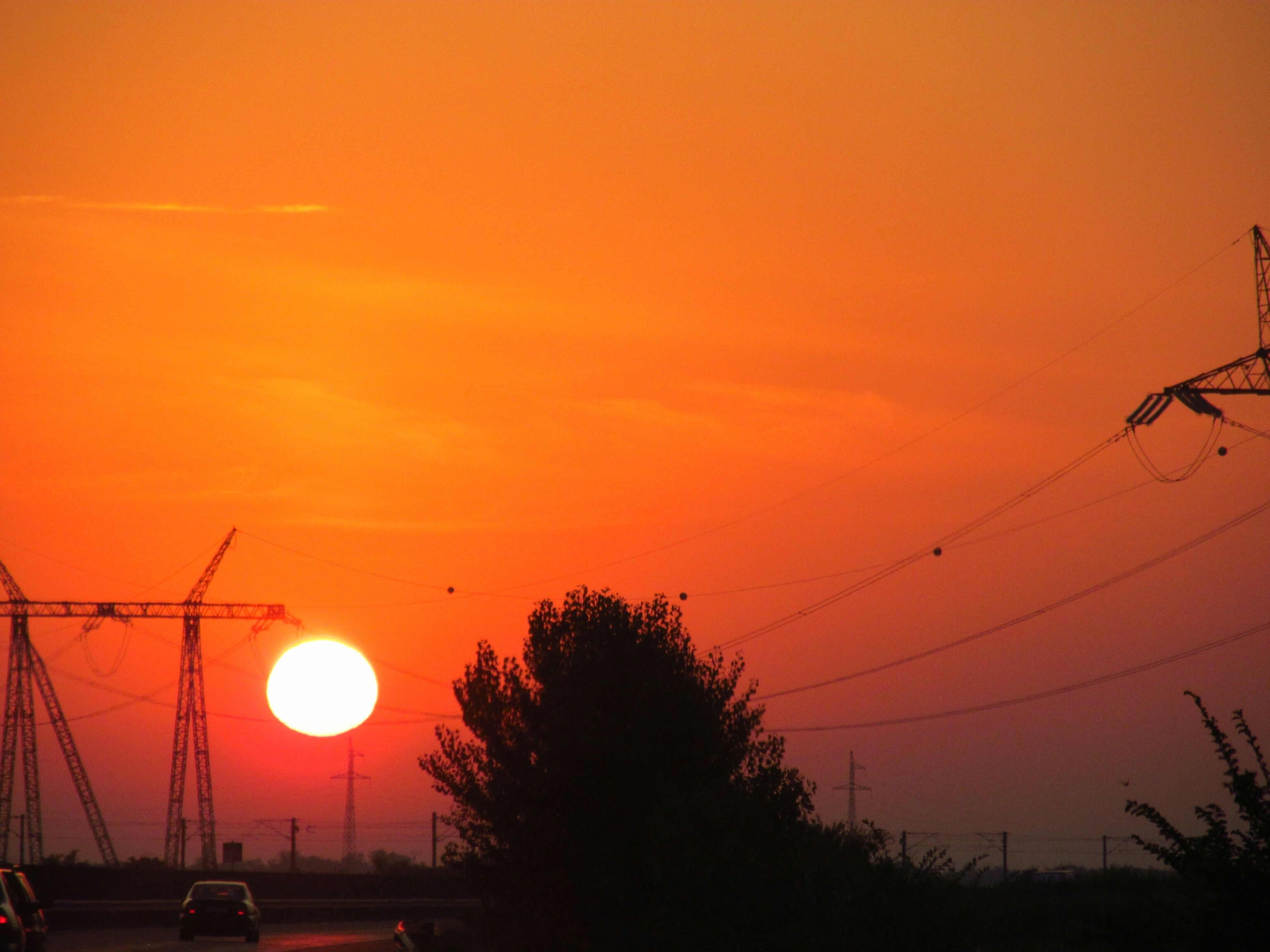 sunset, silhouette, orange color, sun, sky, beauty in nature, scenics, low angle view, tree, tranquility, nature, street light, tranquil scene, idyllic, transportation, power line, electricity, outdoors, no people, dusk