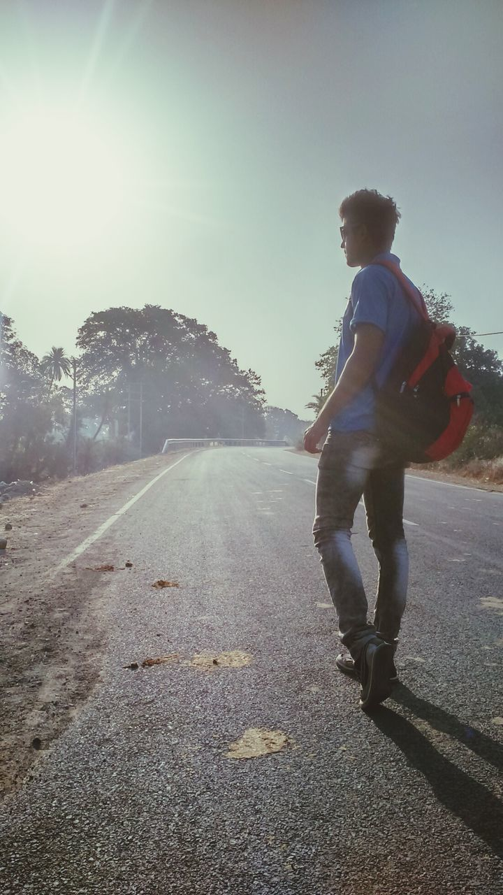 full length, one person, casual clothing, transportation, road, leisure activity, real people, lifestyles, outdoors, sunlight, riding, day, motion, young adult, clear sky, sky, nature, tree, people