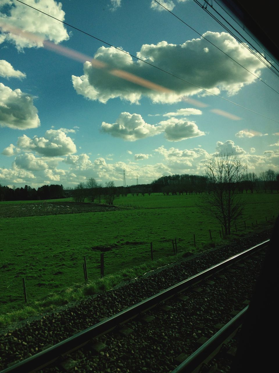 View Of Green Landscape Against Cloudy Sky Seen From Train Window