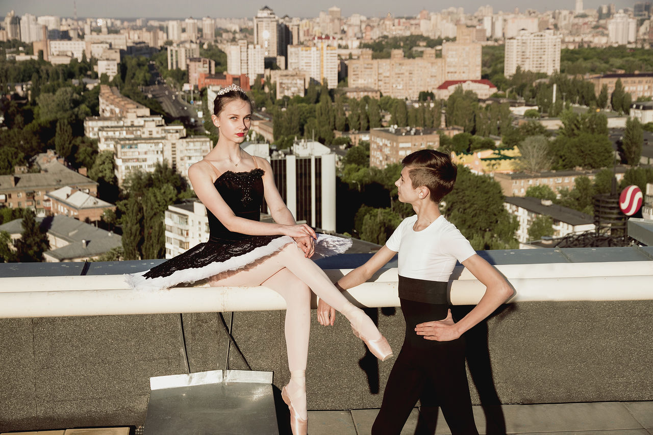 Architecture Ballerina Ballet Boy Ballet Dancer Beautiful Woman Beauty In Nature Building Exterior Built Structure City Cityscape Couple Day Kiev Leisure Activity Lifestyles Outdoors Pointshoes Real People Roof Rooftop Tutu Tutudress Water Young Adult Young Women
