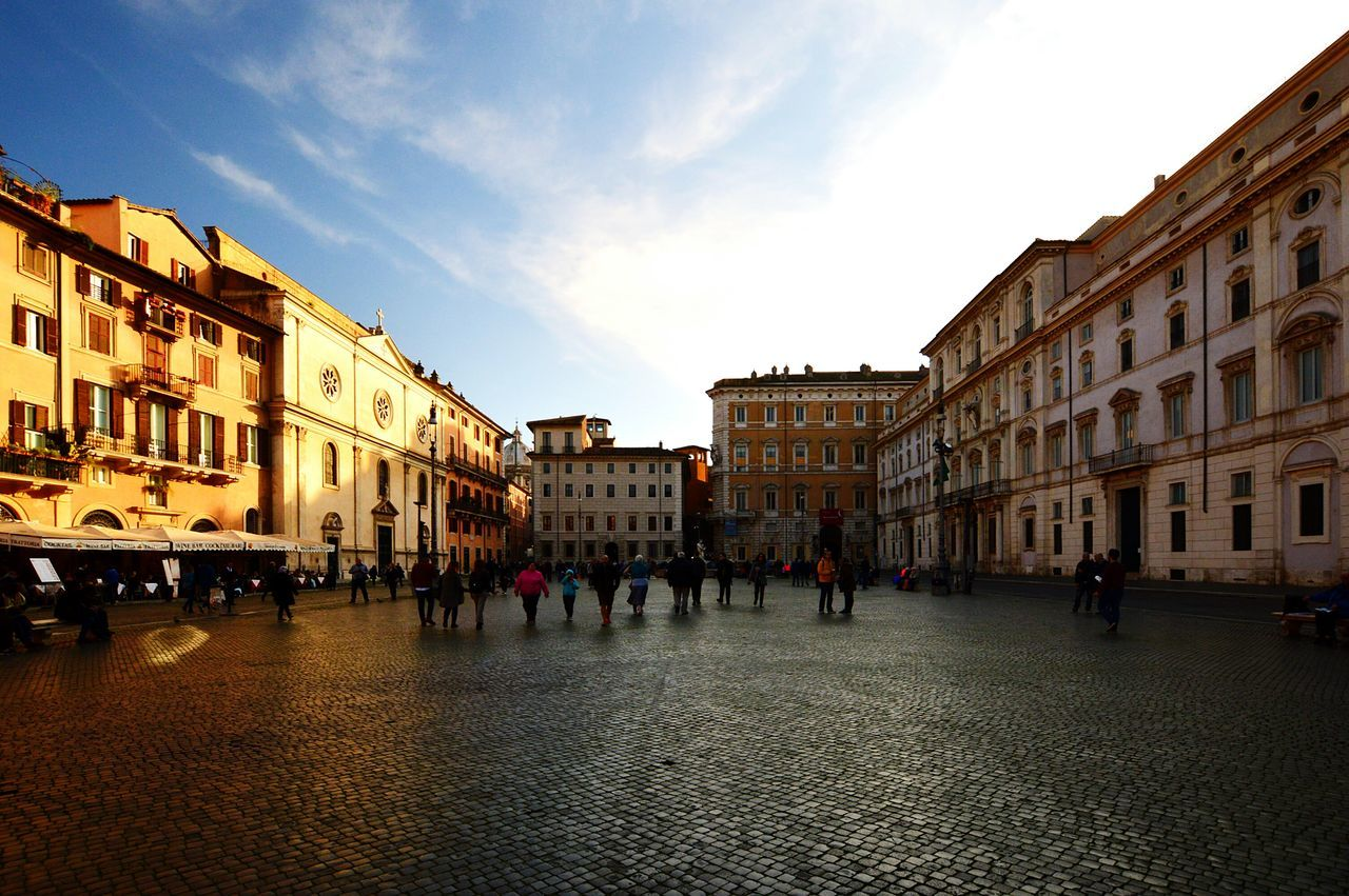 architecture, building exterior, built structure, cobblestone, sky, large group of people, real people, outdoors, day, city, people