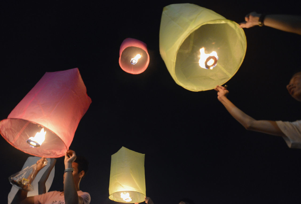 real people, illuminated, night, holding, celebration, balloon, human hand, men, flame, paper lantern, burning, lantern, low angle view, human body part, two people, togetherness, women, outdoors, flying, releasing, helium balloon, people