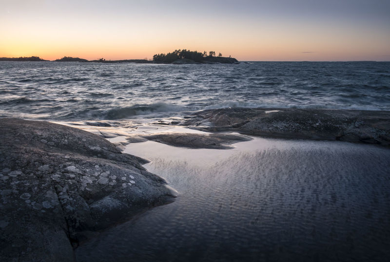 Scenic seascape with nice sunset at windy day in southern Finland Atmospheric Mood Beach Beauty In Nature Blue Cloudless Coast Coastline Colors Evening Landscape Light And Shadow Nature No People Outdoors Rock - Object Scenics Sea Seascape Sky Stone Sunlight Sunset Water Wave Windy
