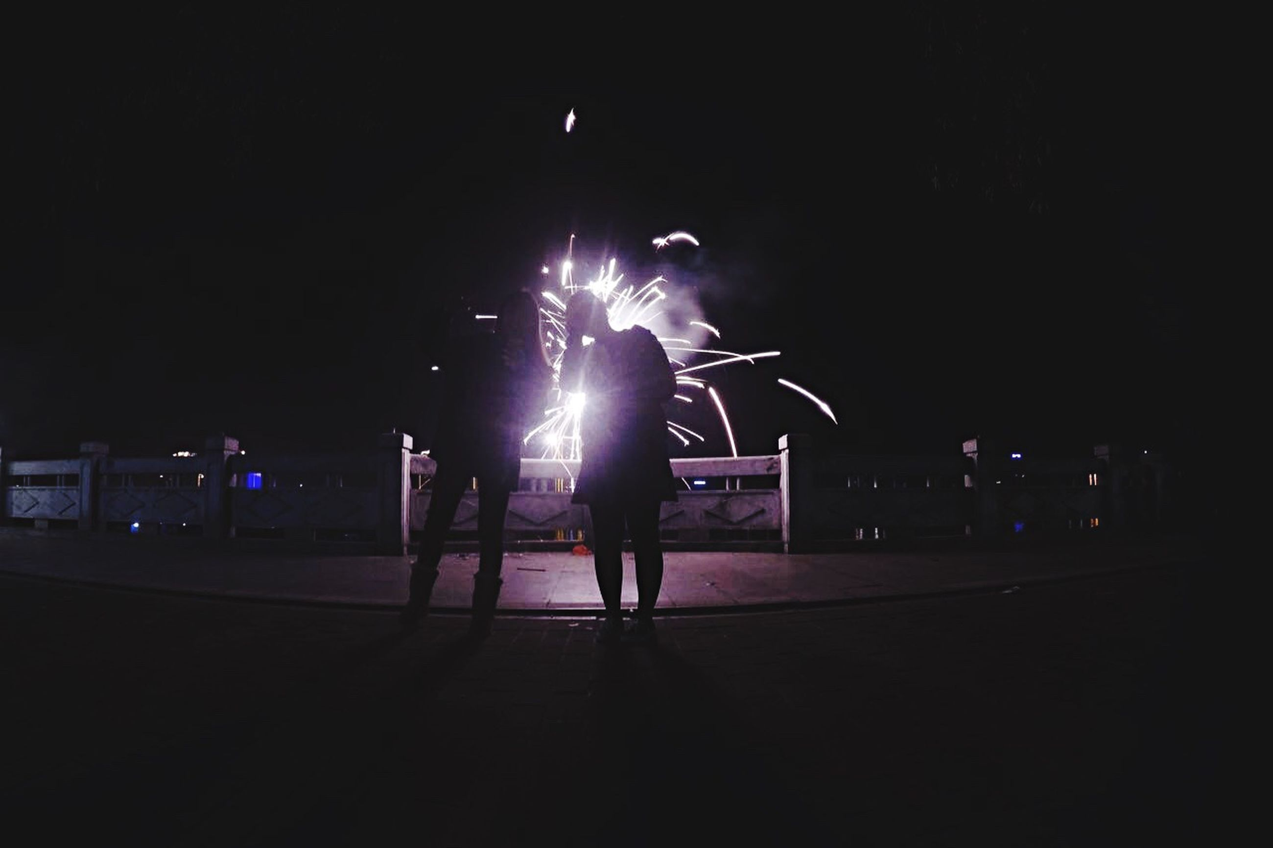 night, illuminated, lifestyles, leisure activity, men, arts culture and entertainment, full length, performance, motion, glowing, light - natural phenomenon, lighting equipment, enjoyment, standing, long exposure, togetherness, rear view, person, dark