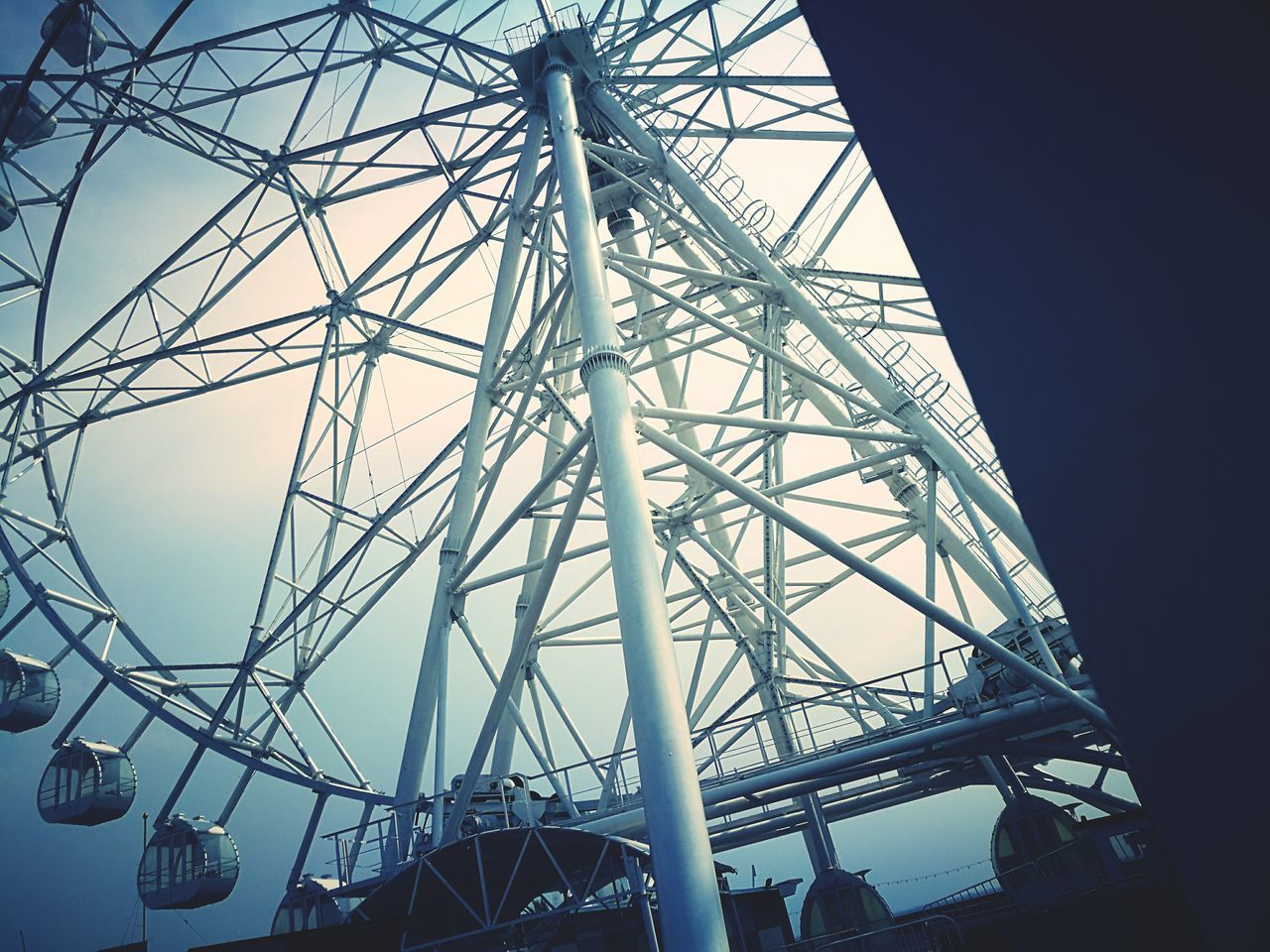 low angle view, connection, built structure, ferris wheel, arts culture and entertainment, big wheel, no people, amusement park, day, outdoors, sky, architecture