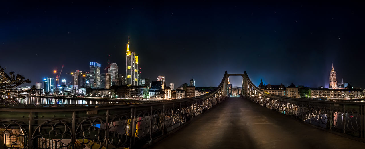 This is the skyline of Frankfurt am Main and the bridge is called Eisernen Steg from 1868 Bridge Panorama Night Photography Skyline Cityscapes Frankfurt Mainhattan Eisernersteg Night Lights Seeing The Sights Landscapes With WhiteWall Cities At Night