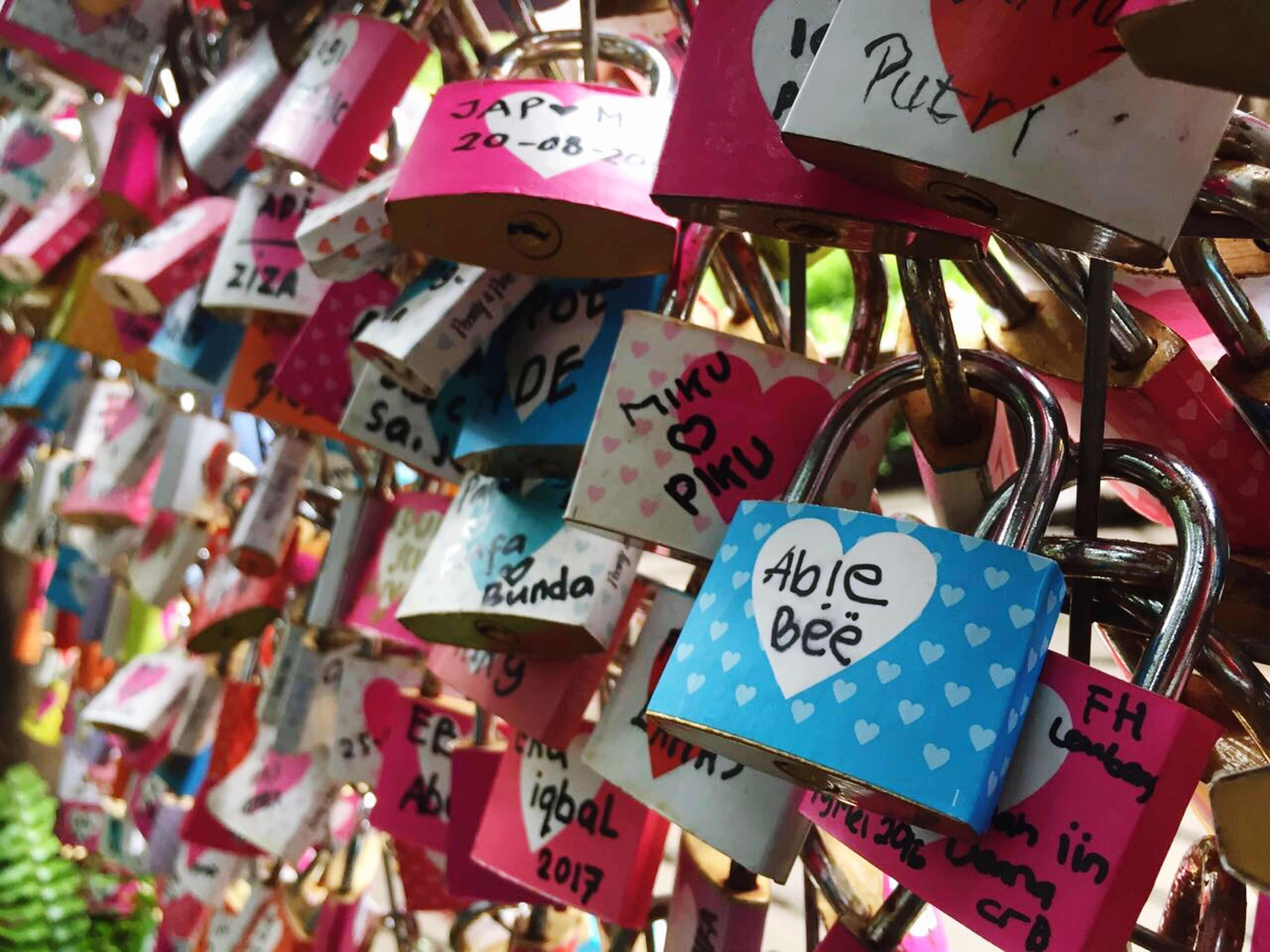 text, communication, large group of objects, padlock, hanging, abundance, variation, western script, close-up, luck, lock, multi colored, focus on foreground, choice, full frame, metal, no people, day, backgrounds, safety