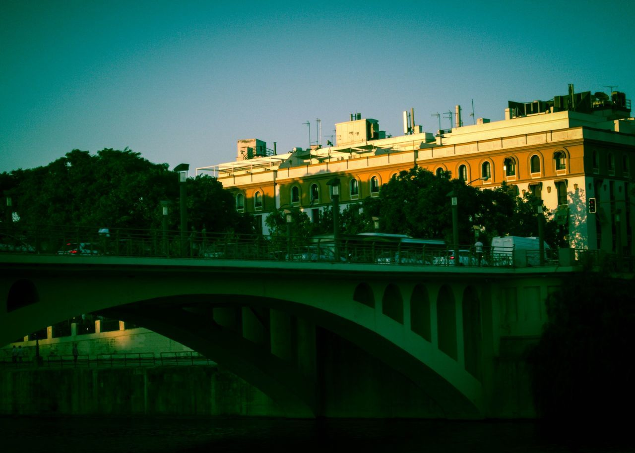 Arch Bridge Over River By Buildings Against Clear Sky