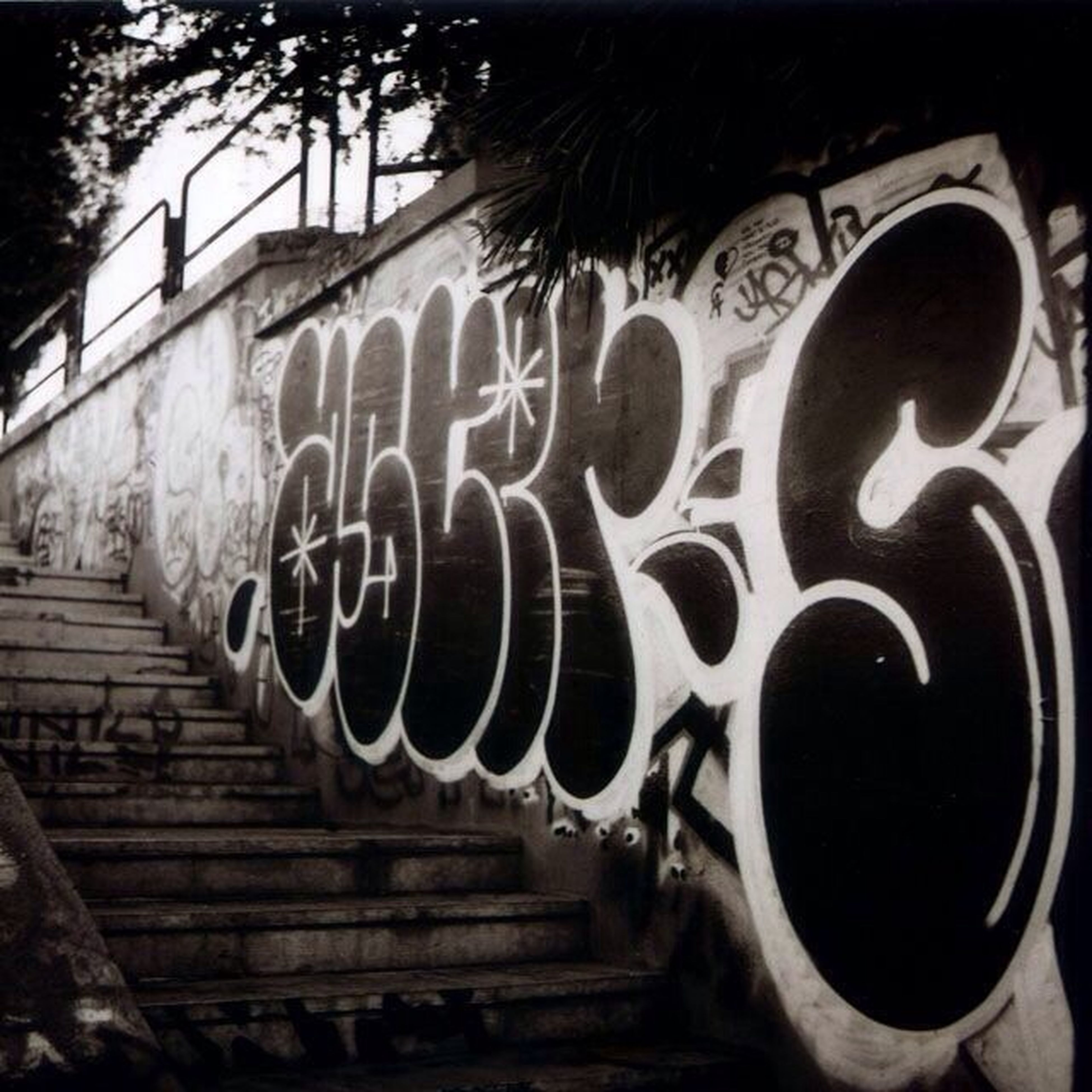 steps, built structure, architecture, railing, staircase, outdoors, steps and staircases, tree, day, building exterior, one person, close-up, graffiti, transportation, sunlight, old, part of, wall - building feature, pattern