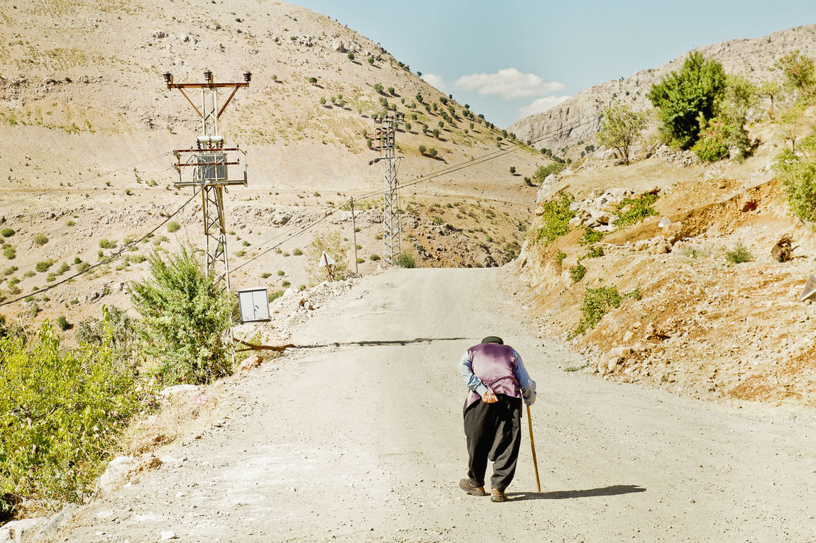Old man going along a unpaved dusty road with the help of a walking stick on a hot summer day somewhere in Central Turkey. Alone Arid Climate Day Getting Away From It All Landscape Mountain Mountain Range Non-urban Scene Old Man Outdoors Remote Remote Location Traveling Valley Walking Stick