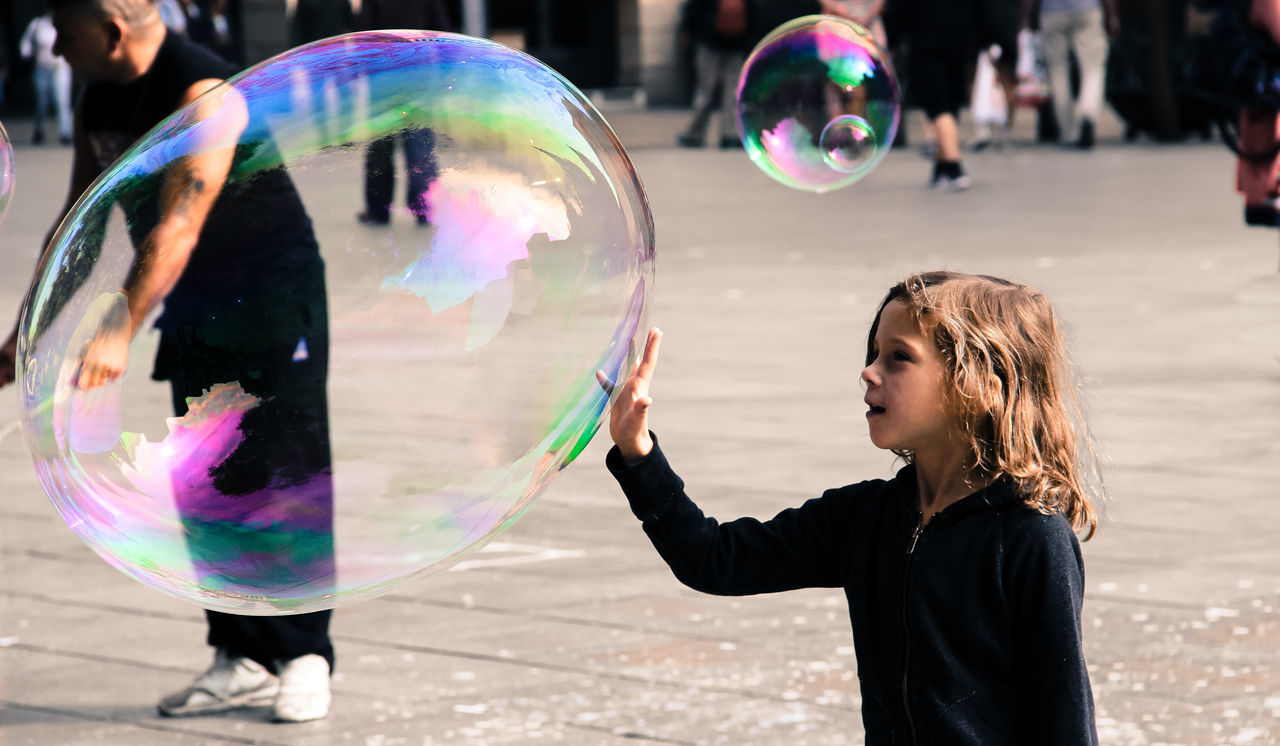 Chance Encounters Sweet little moment. Bubble Bubble Wand Day Fragility Fun Kid Mesmerized Multi Colored Outdoors People Soap Sud Standing Streetphotography Sweet Urban Waist Up Embrace Urban Life Enjoy The New Normal Traveling Home For The Holidays EyeEmNewHere