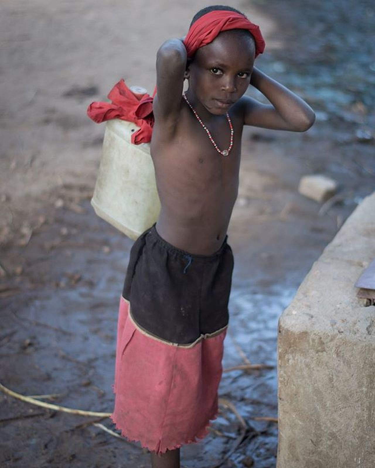 The drought is upon us and it often falls on the kids to carry the water home with mama. This little one doesn't have shoes but is friendly and polite. Dontgiveyourkidseverythingtheyaskfor Waterislife Child Samburu Kenya Africa photooftheday igkenya nomad desert wearespoiled
