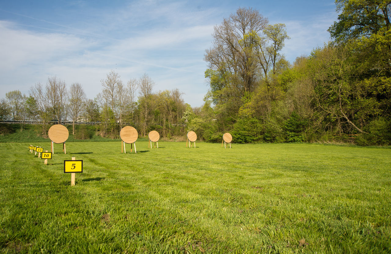 Empty archery range with distance tags on the left Archery Range Archery Target Day Grass Green Color No People Outdoors Sky Sports Tree