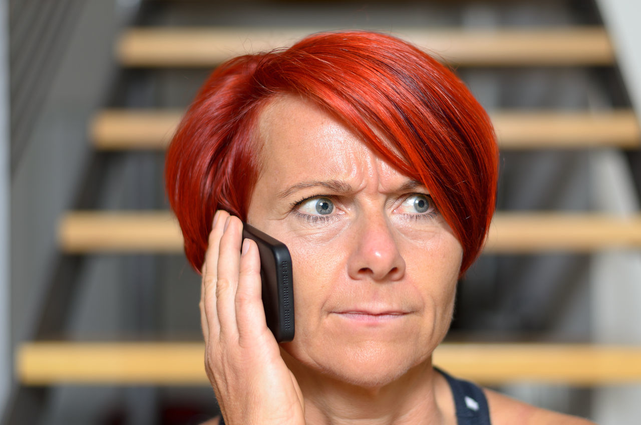 Woman Talking On Mobile Phone While Sitting Against Stairs