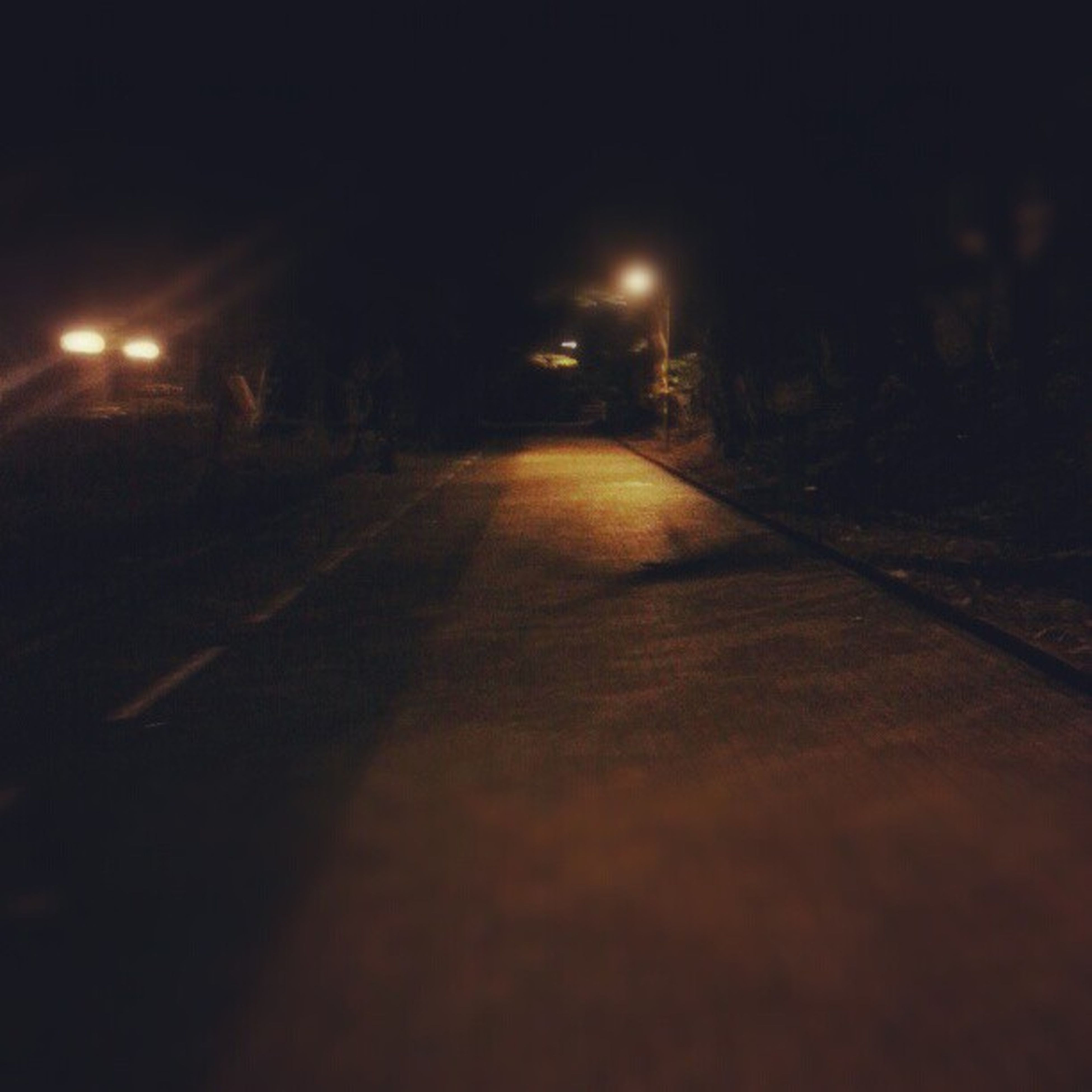 night, illuminated, the way forward, diminishing perspective, vanishing point, street light, dark, lighting equipment, road, street, surface level, empty, transportation, light - natural phenomenon, no people, outdoors, long, built structure, copy space, architecture