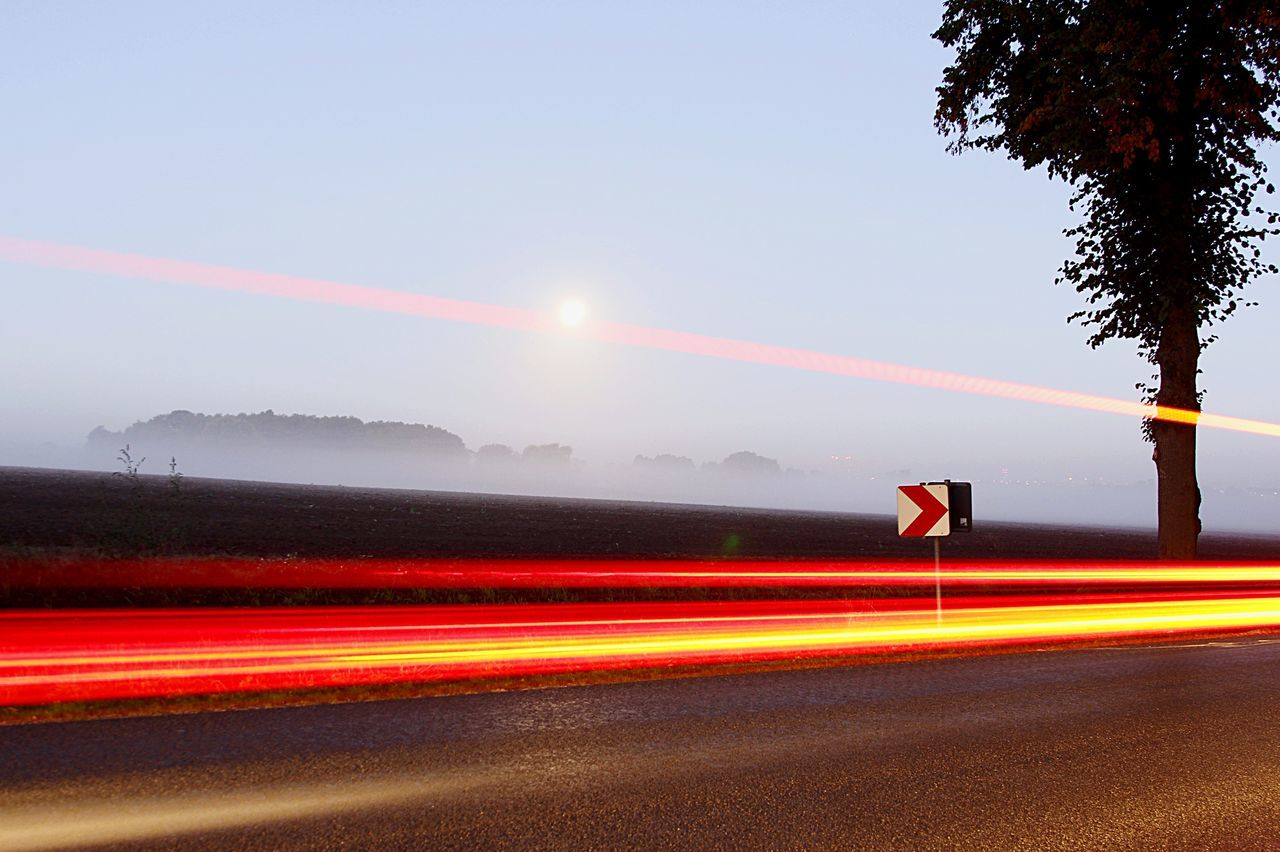 Light Trail On Highway Against Sky At Foggy Dawn