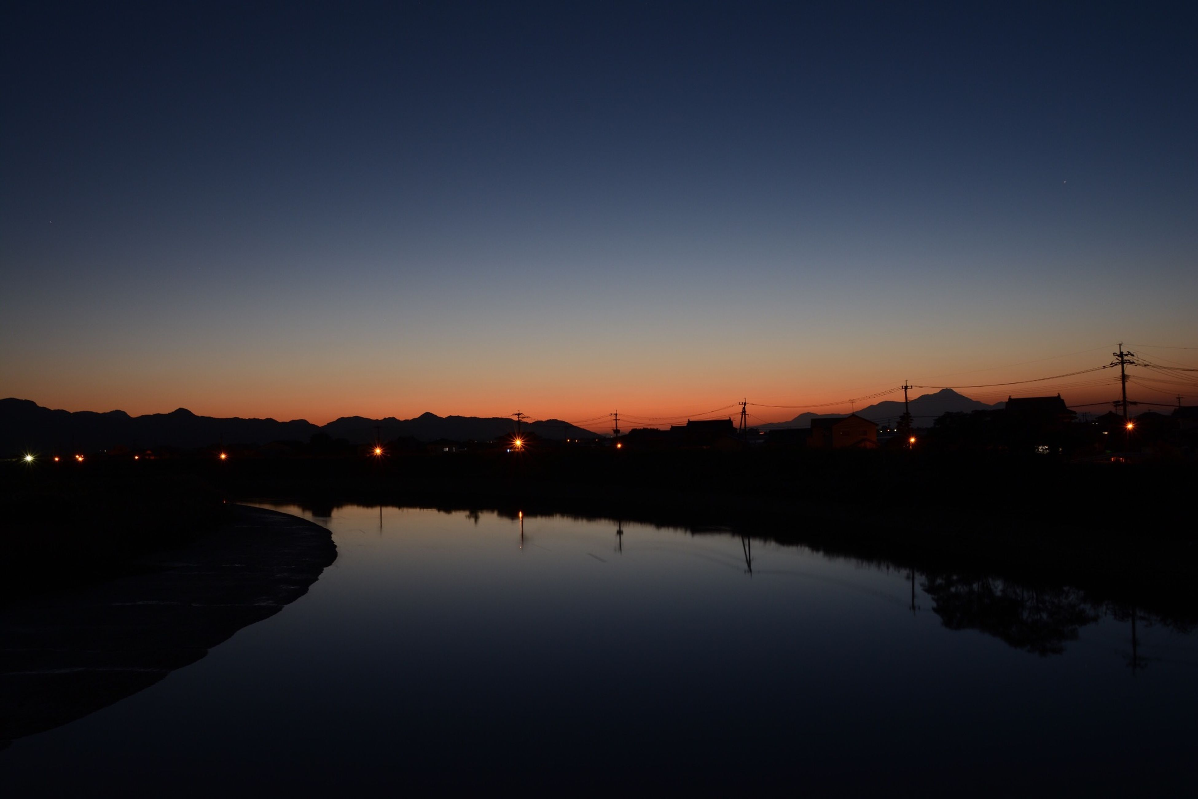 reflection, sunset, illuminated, water, clear sky, silhouette, built structure, copy space, architecture, waterfront, dusk, connection, tranquility, night, sky, river, standing water, building exterior, tranquil scene, street light