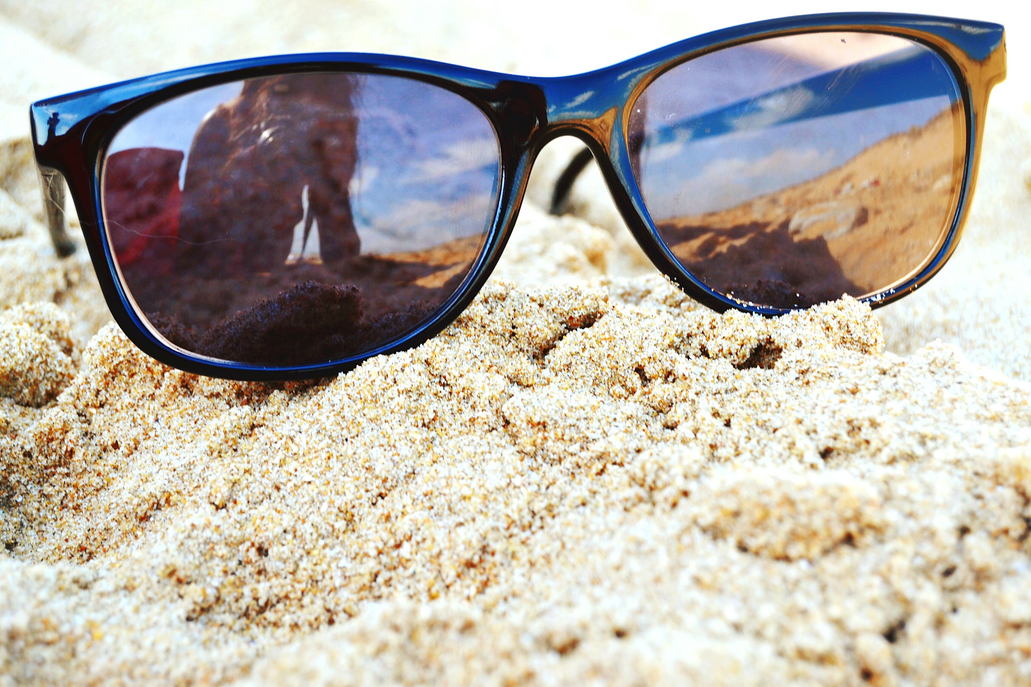 reflection, transparent, sunglasses, beach, glass - material, close-up, sand, surface level, tranquility, vision, water, non-urban scene, nature, shore, glasses, scenics, eyesight, tranquil scene, no people, soil, beauty in nature, sea, cloud - sky