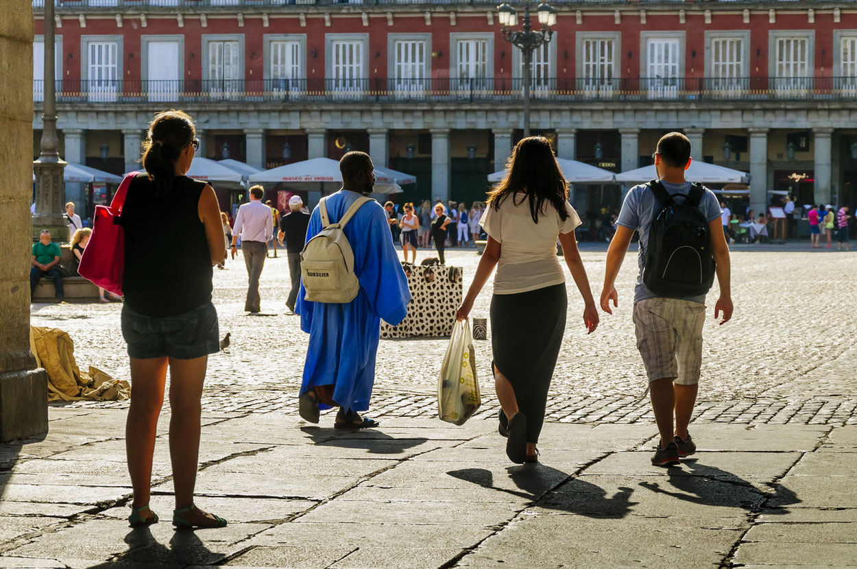 A view of a young woman tourist in shorts, a couple and a a North African wearing a blue tunic entering Plaza Mayor in Madrid. Casual Clothing City Full Length Leisure Activity Madrid People Plaza Mayor Real People Rear View Street Streetphotography Travel Walking Women