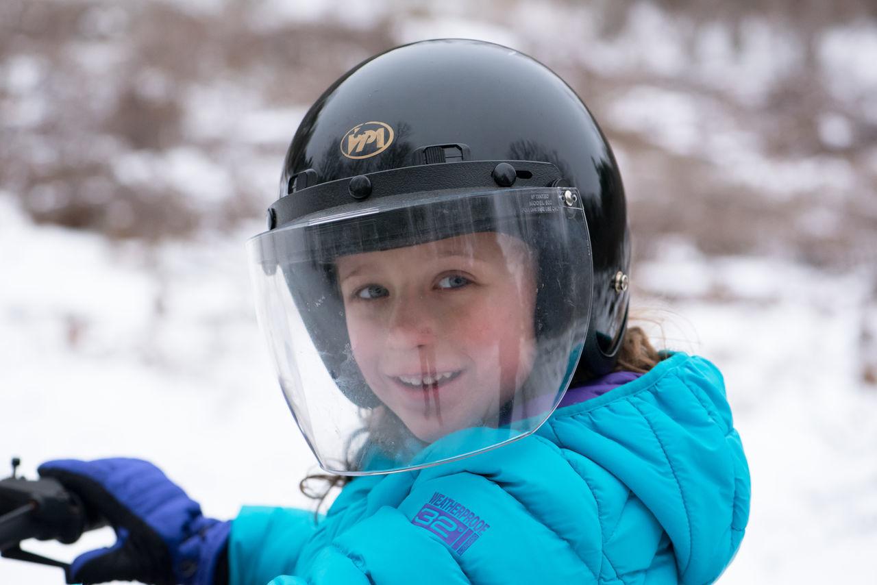 Portrait Of Girl Wearing Crash Helmet On Snow Covered Field