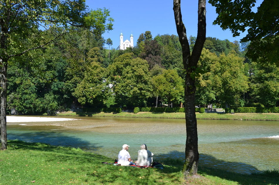 Beauty In Nature Church Day Grass Green Color Growth Isar Nature Outdoors People Real People River Riverside Scenics Sitting Sitting By The River Sky Summertime Tree Two Churchtowers, Two Ladies Two Ladies Two People Water