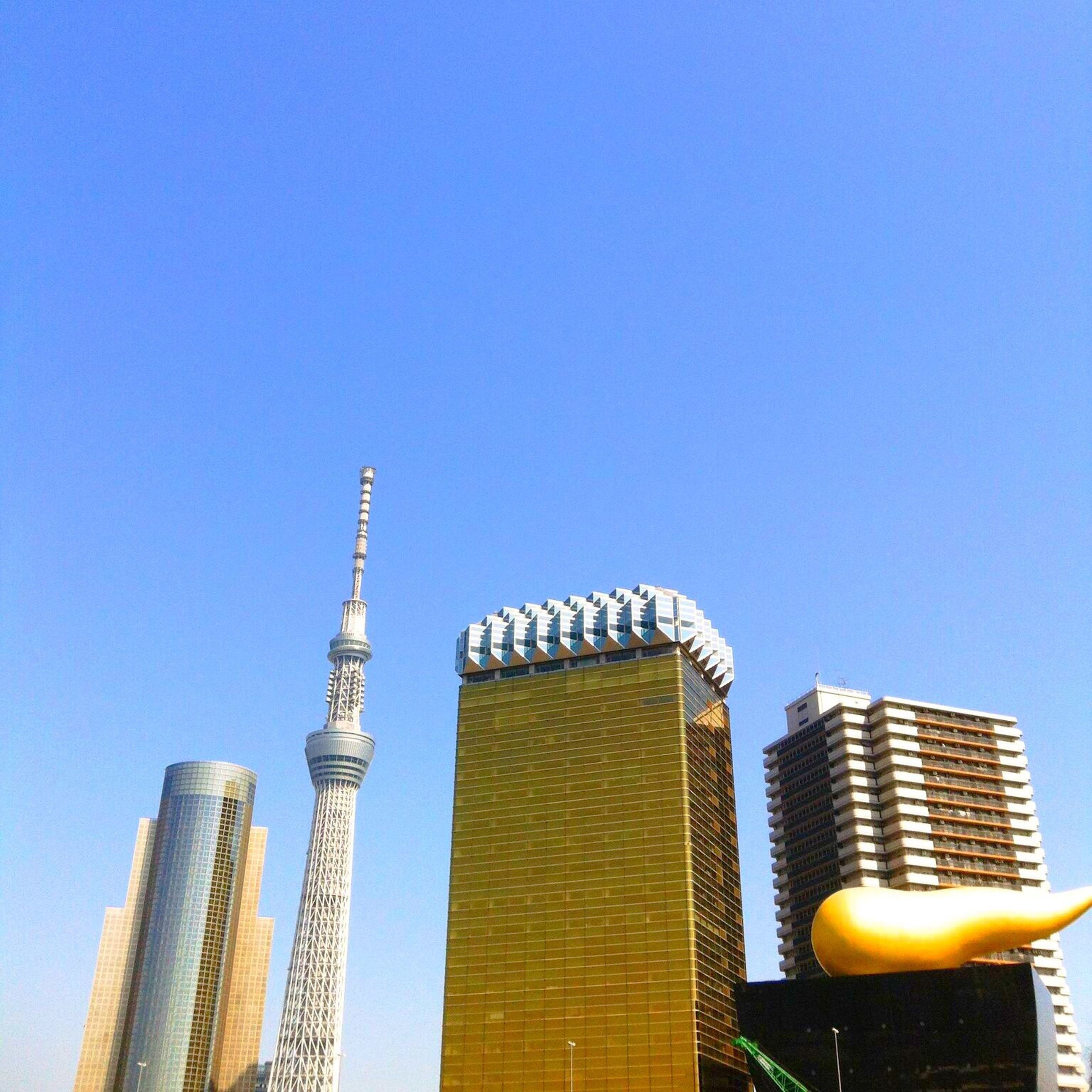 clear sky, architecture, built structure, building exterior, low angle view, copy space, blue, tall - high, tower, city, yellow, modern, skyscraper, famous place, travel destinations, outdoors, capital cities, no people, building, international landmark