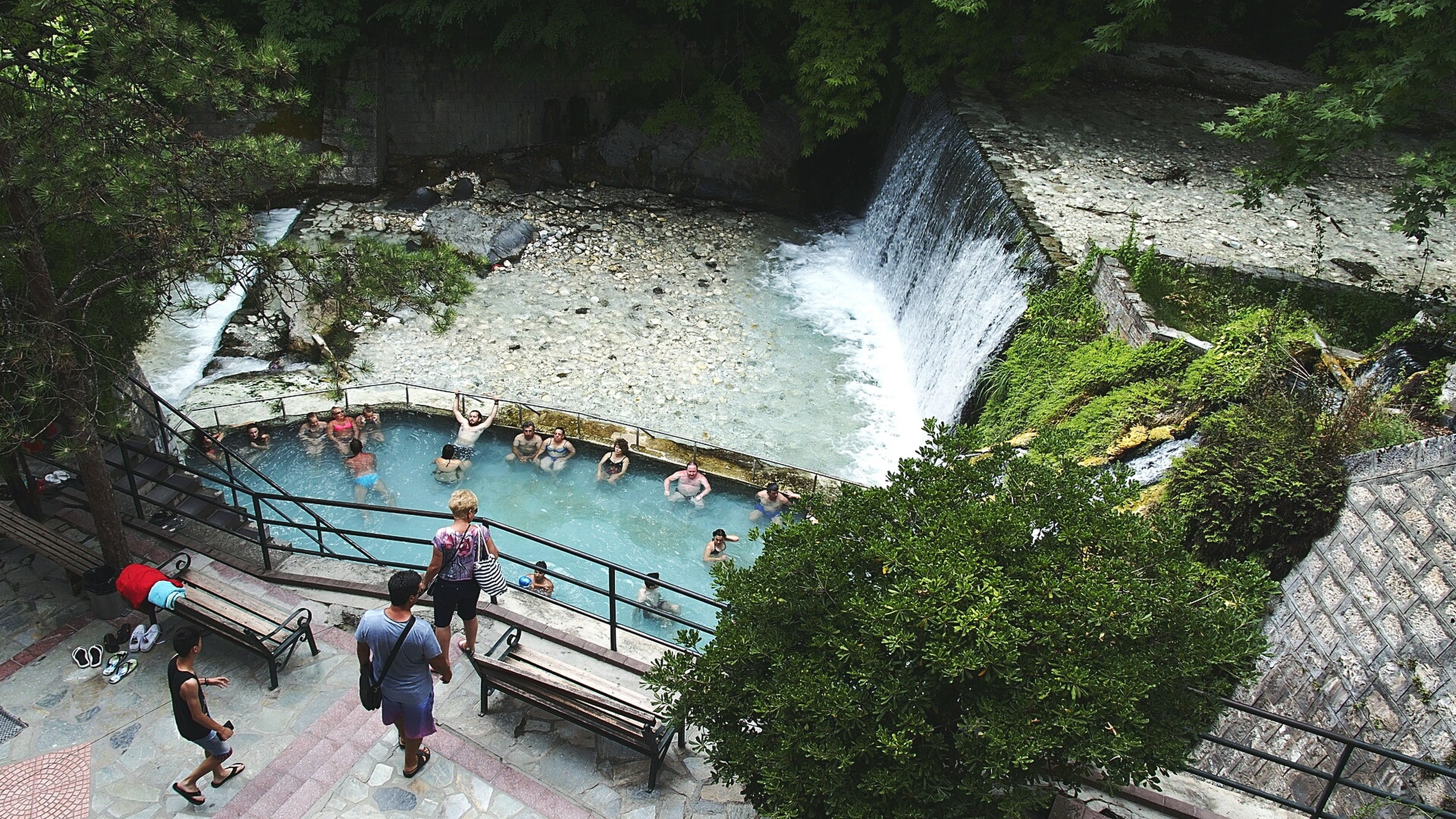 men, lifestyles, water, leisure activity, large group of people, person, high angle view, motion, tree, medium group of people, travel, mixed age range, tourist, steps, walking, rock - object, day, waterfall, outdoors