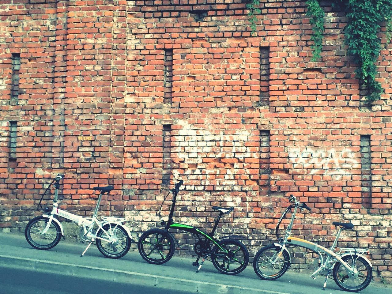brick wall, bicycle, mode of transport, wall - building feature, transportation, stationary, outdoors, no people, day, bicycle rack, land vehicle, architecture