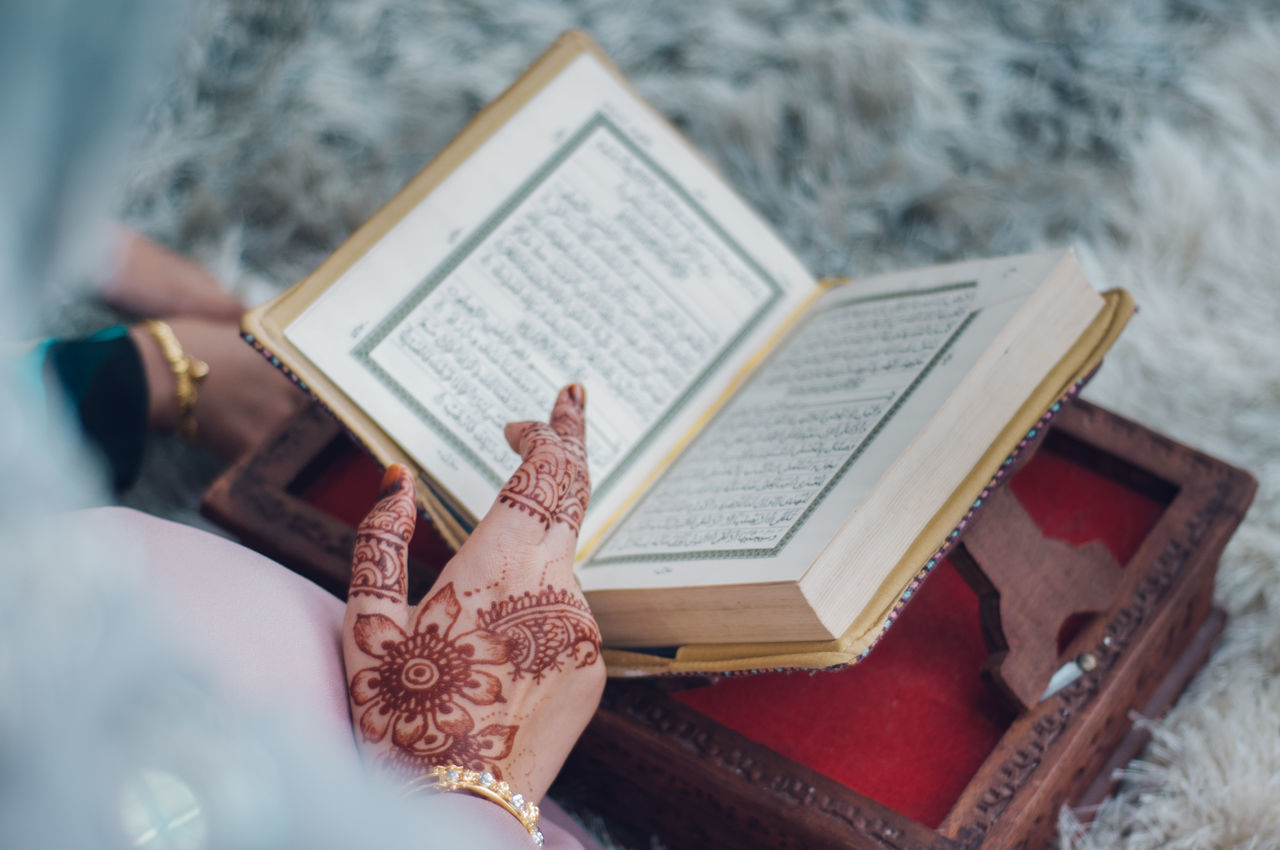 Adult Ancient Civilization Book Close-up Day Henna Tattoo High Angle View Holding Human Body Part Human Hand Indoors  Musical Note One Person People Quran Real People Religion Spirituality